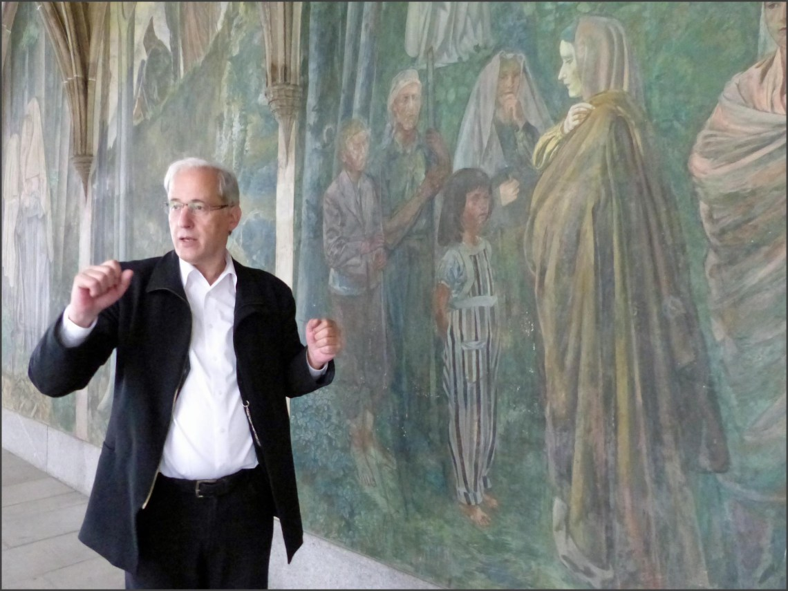 Man standing in front of frescoes, talking