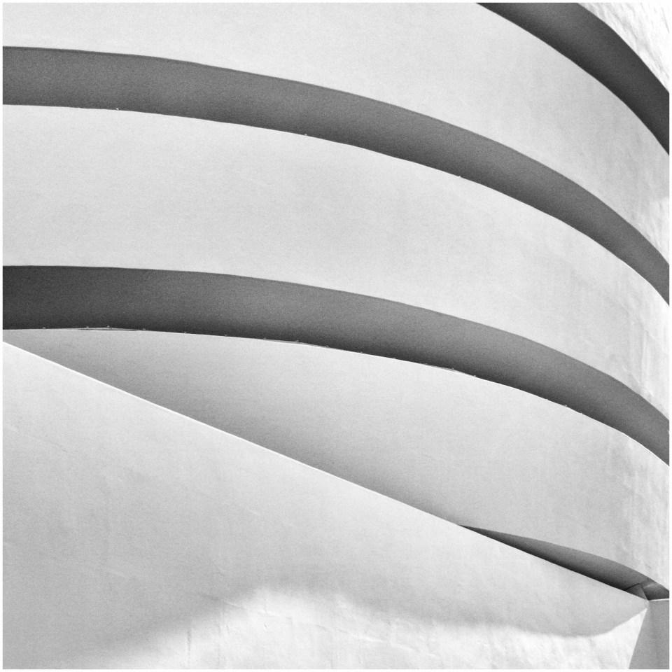 Black and white photo of white building with curves