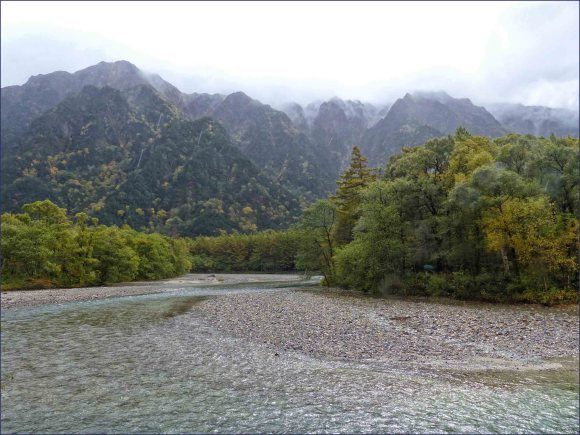 Grey river surrounded by mountains in low cloud