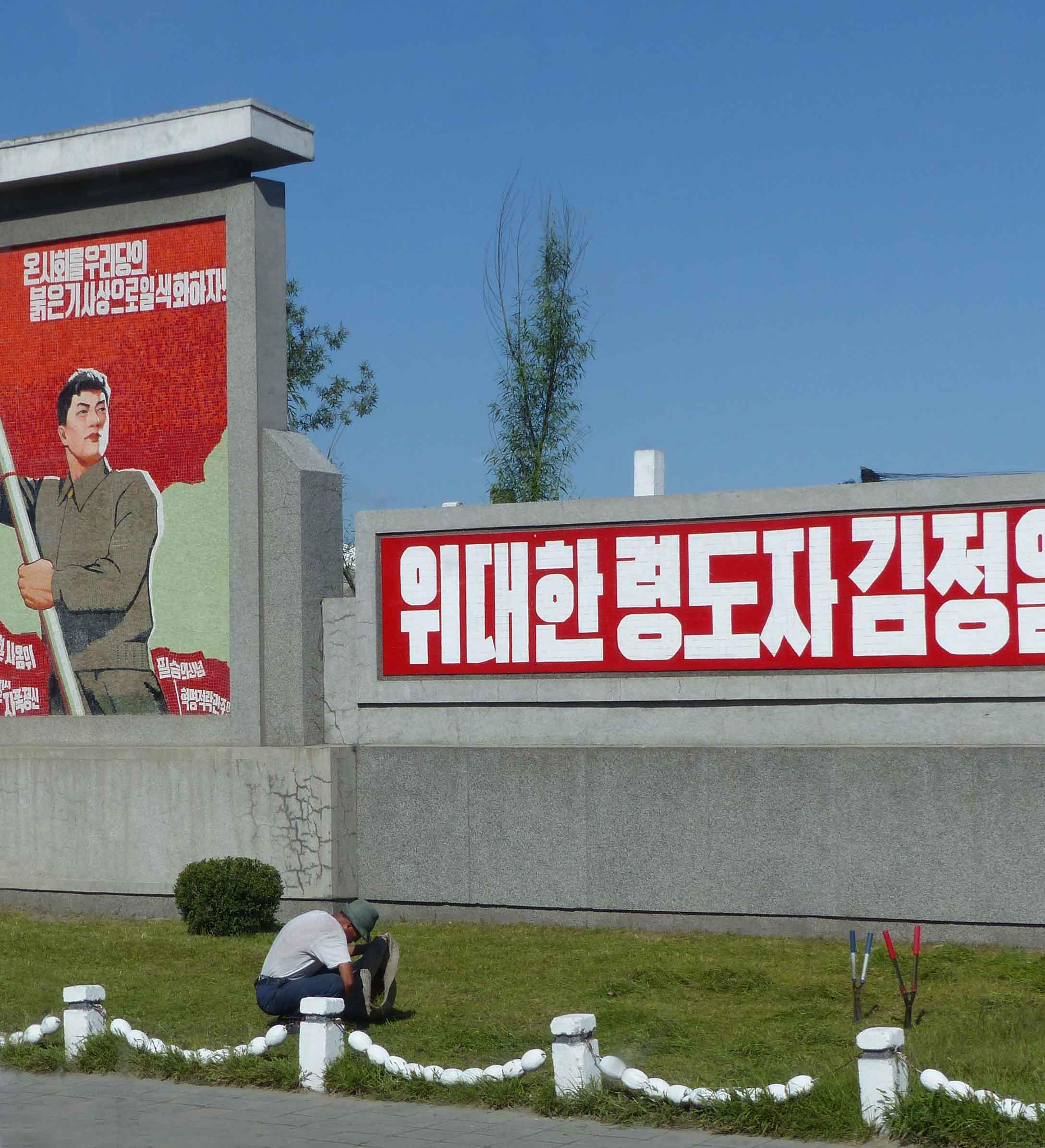 Man gardening in front of propaganda poster