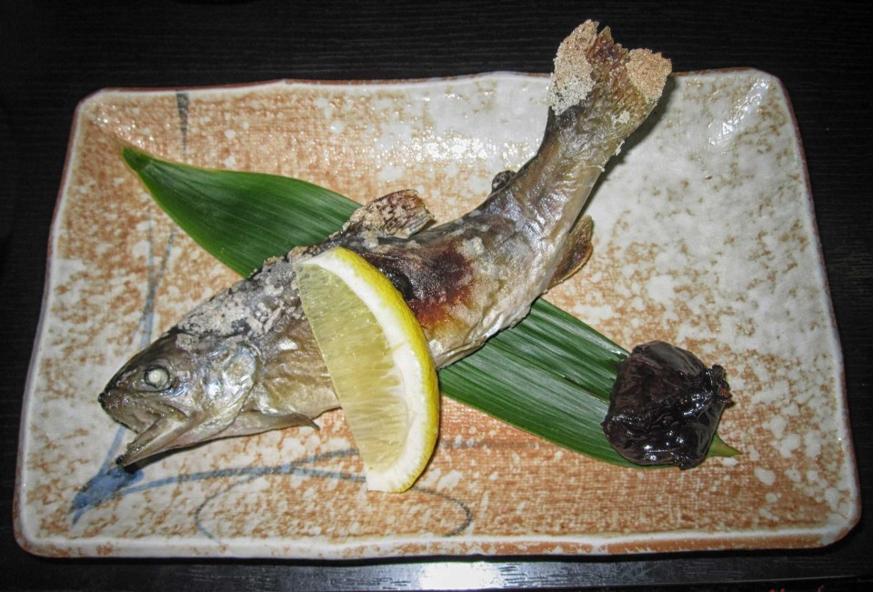 Whole small fish with lemon wedge