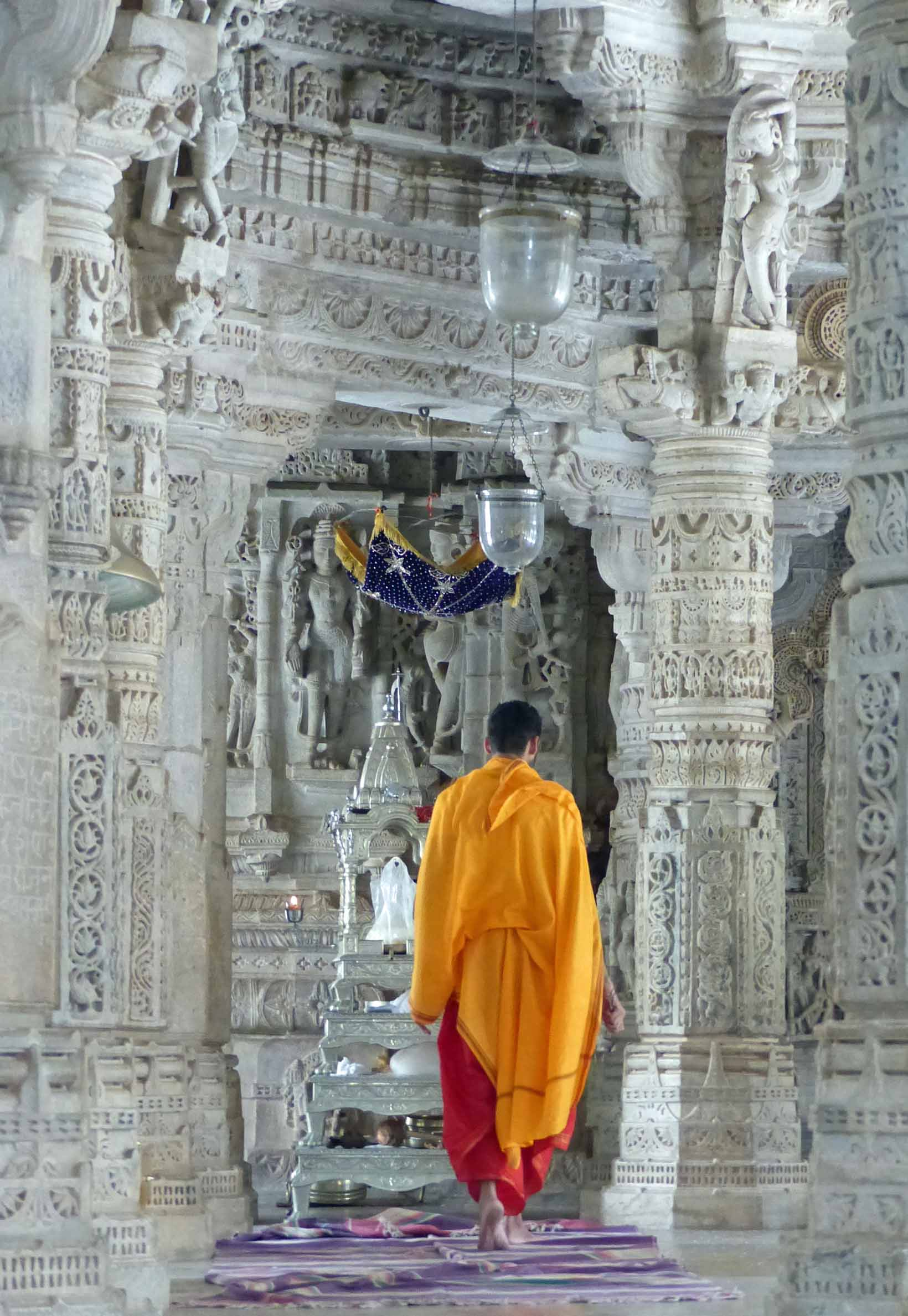 Monk in saffron robes among carved pillars