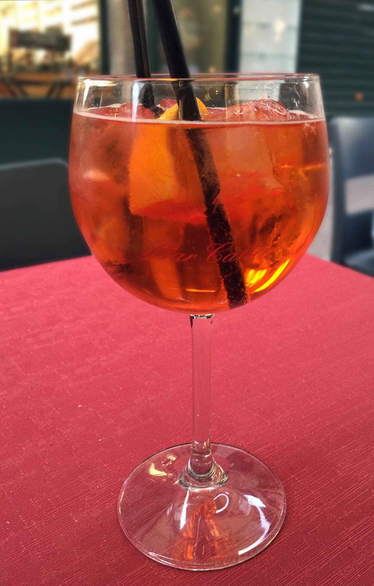 Glass of orange coloured drink on red table cloth