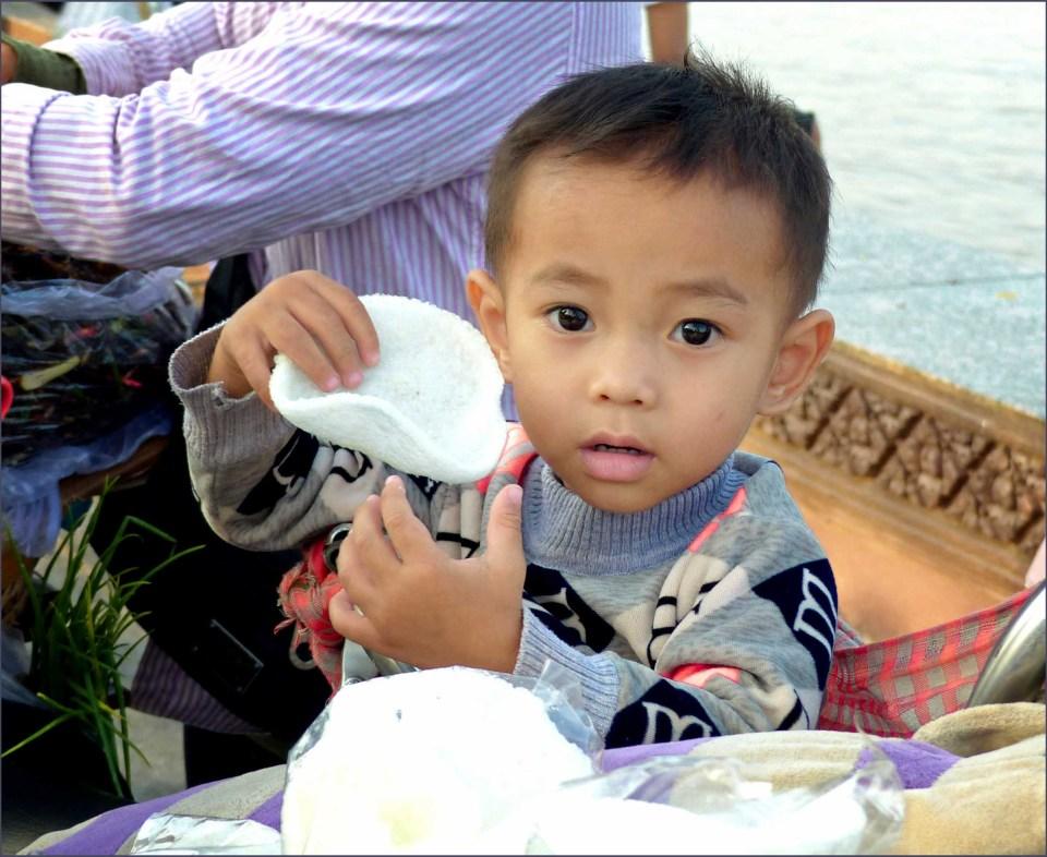 Little boy staring at camera, holding cracker