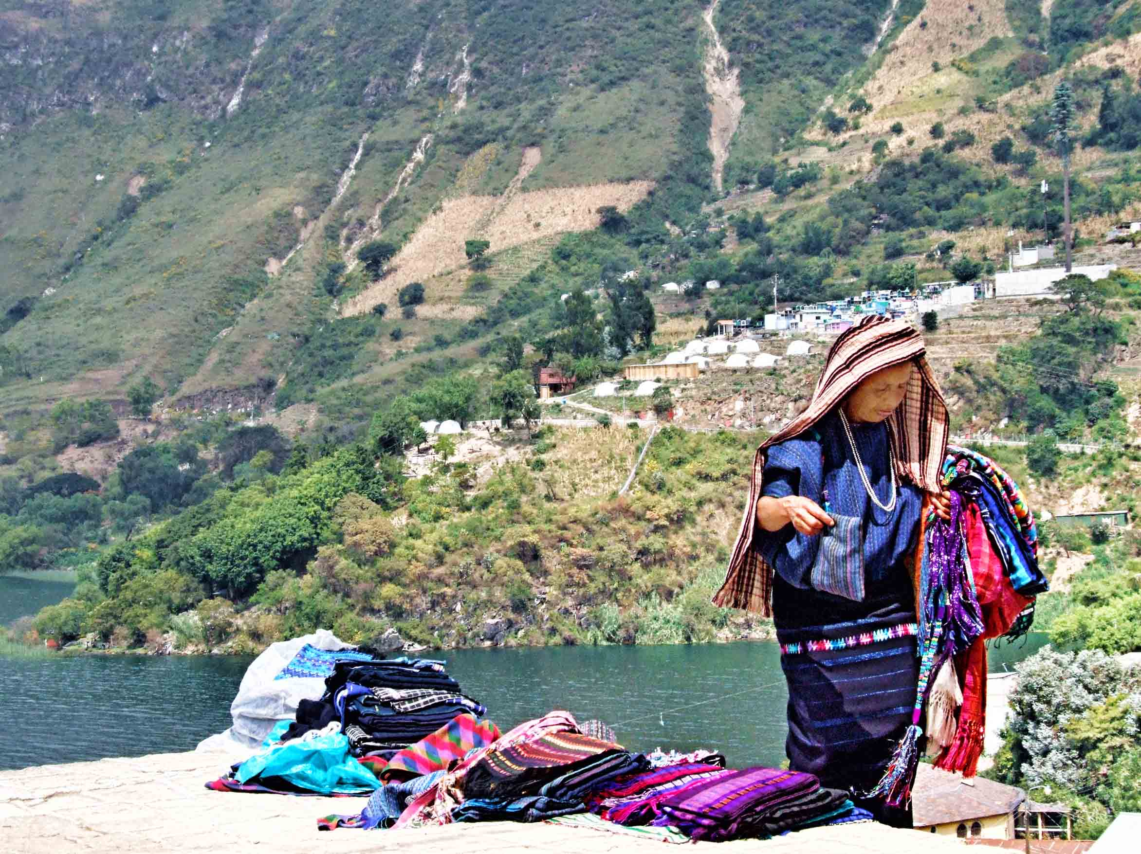 Woman in traditional blue clothing by a lake