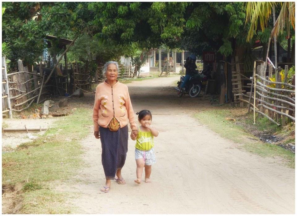 Old lady and child on sandy village street
