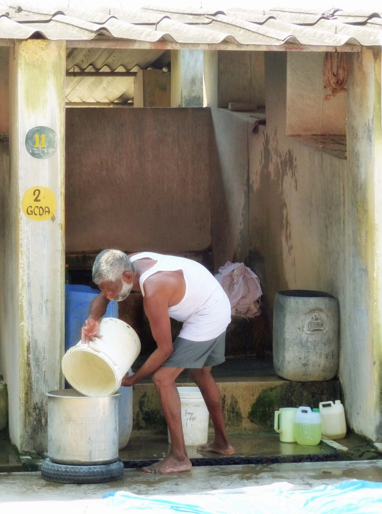 Man pouring water in a stone building