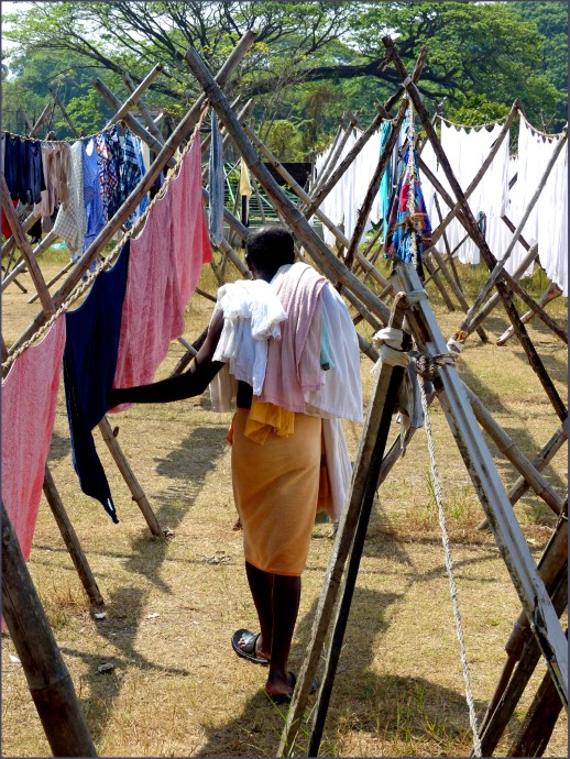 Rows of drying washing and man carrying cloth