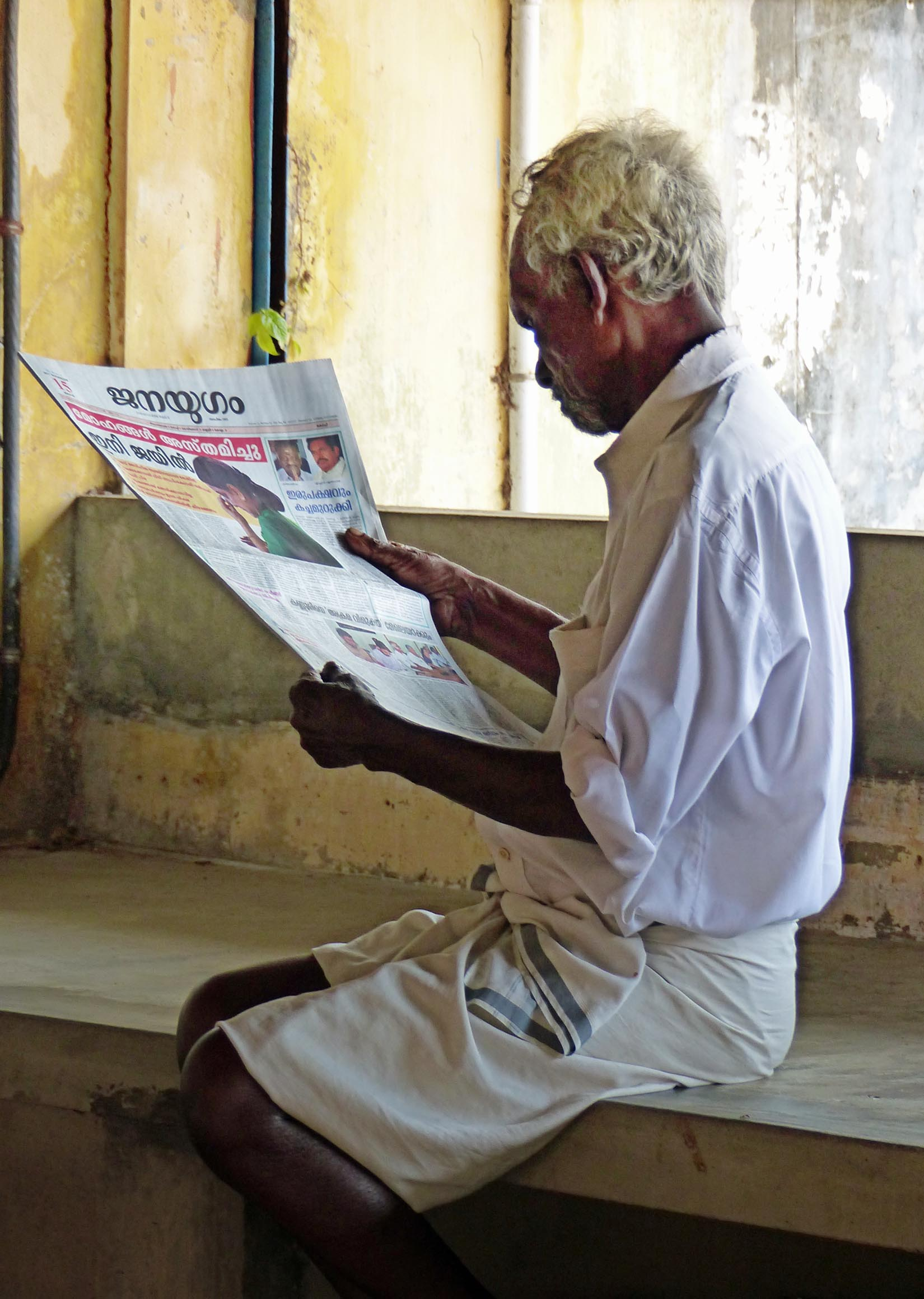 Man reading a newspaper on a stone seat