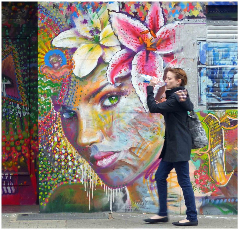 Young lady passing colourful mural