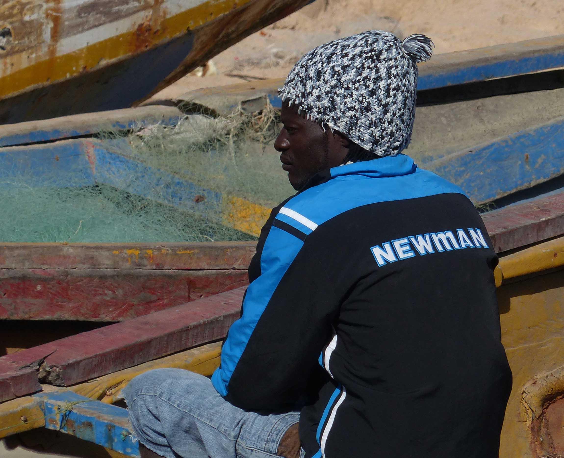 Man sitting among boats on the beach