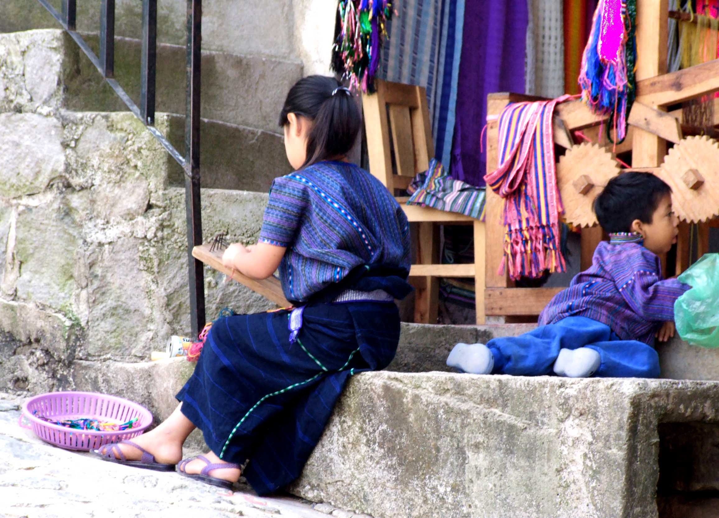 Girl in traditional blue clothing weaving om a small handloom