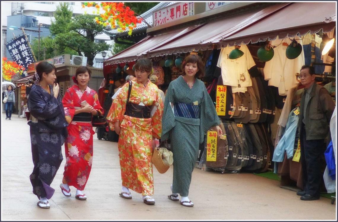 Four women in kimonos passing a shop