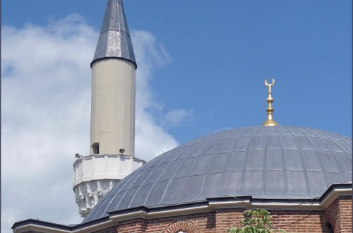Exterior of brick mosque with dome and minaret