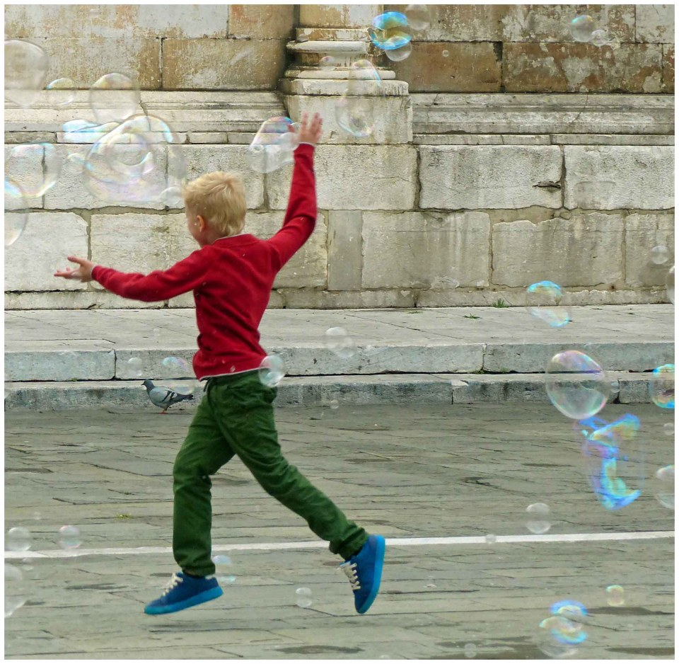 Boy in red jumper chasing soap bubbles