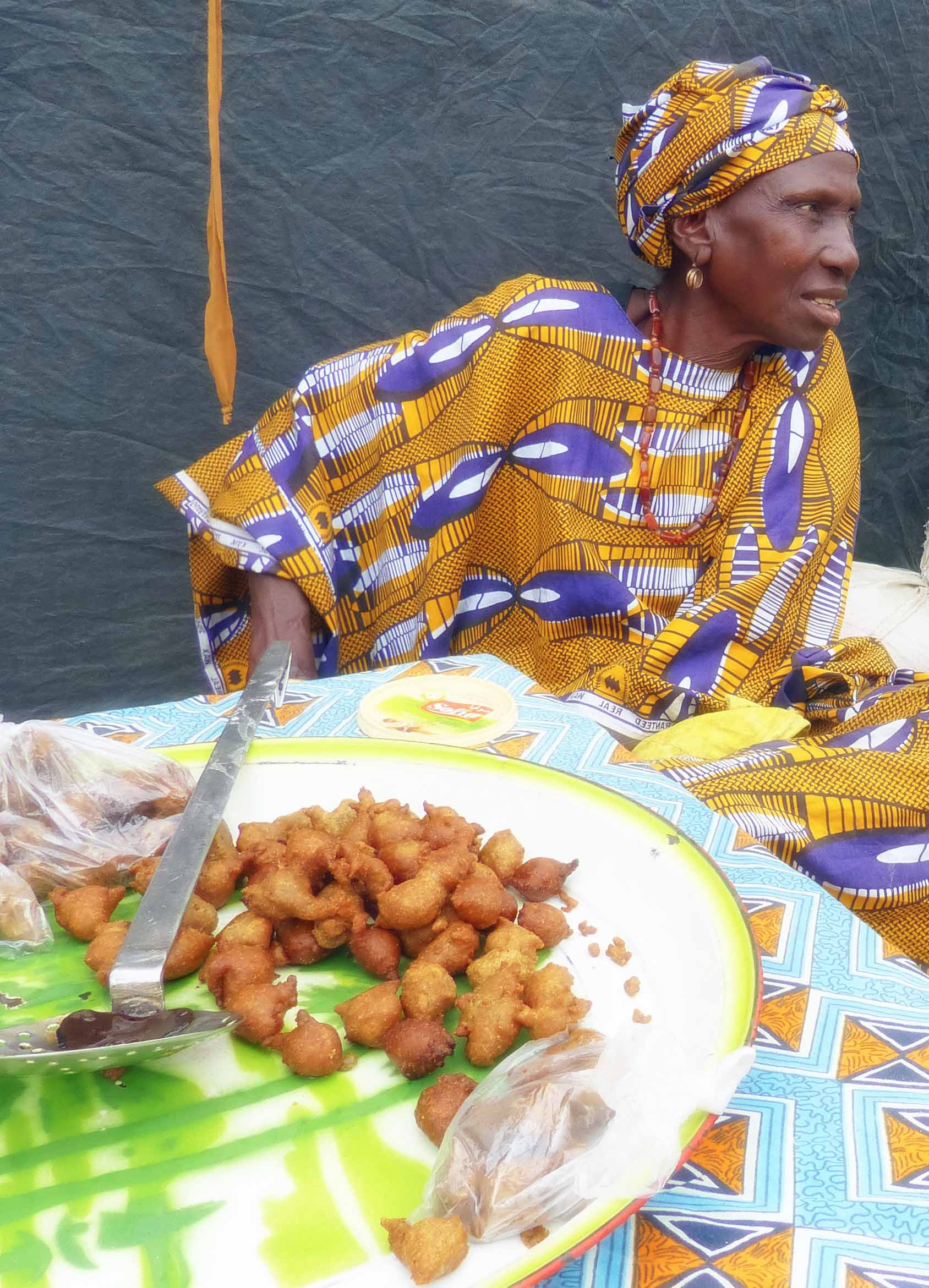 Lady in African dress selling fried food