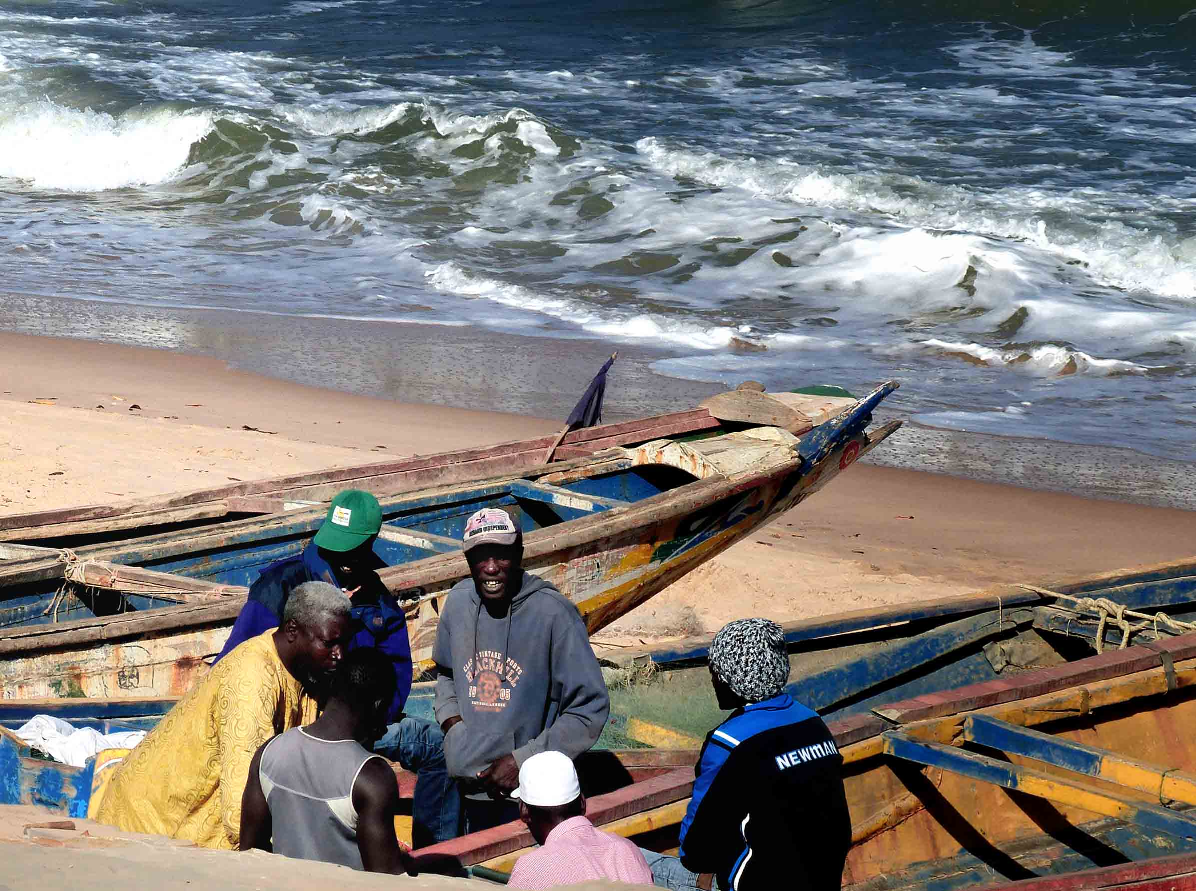 Group of men sitting among fishing boats on a beach