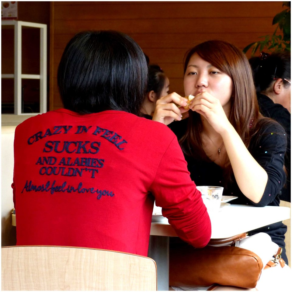 Girl in red t-shirt at a table