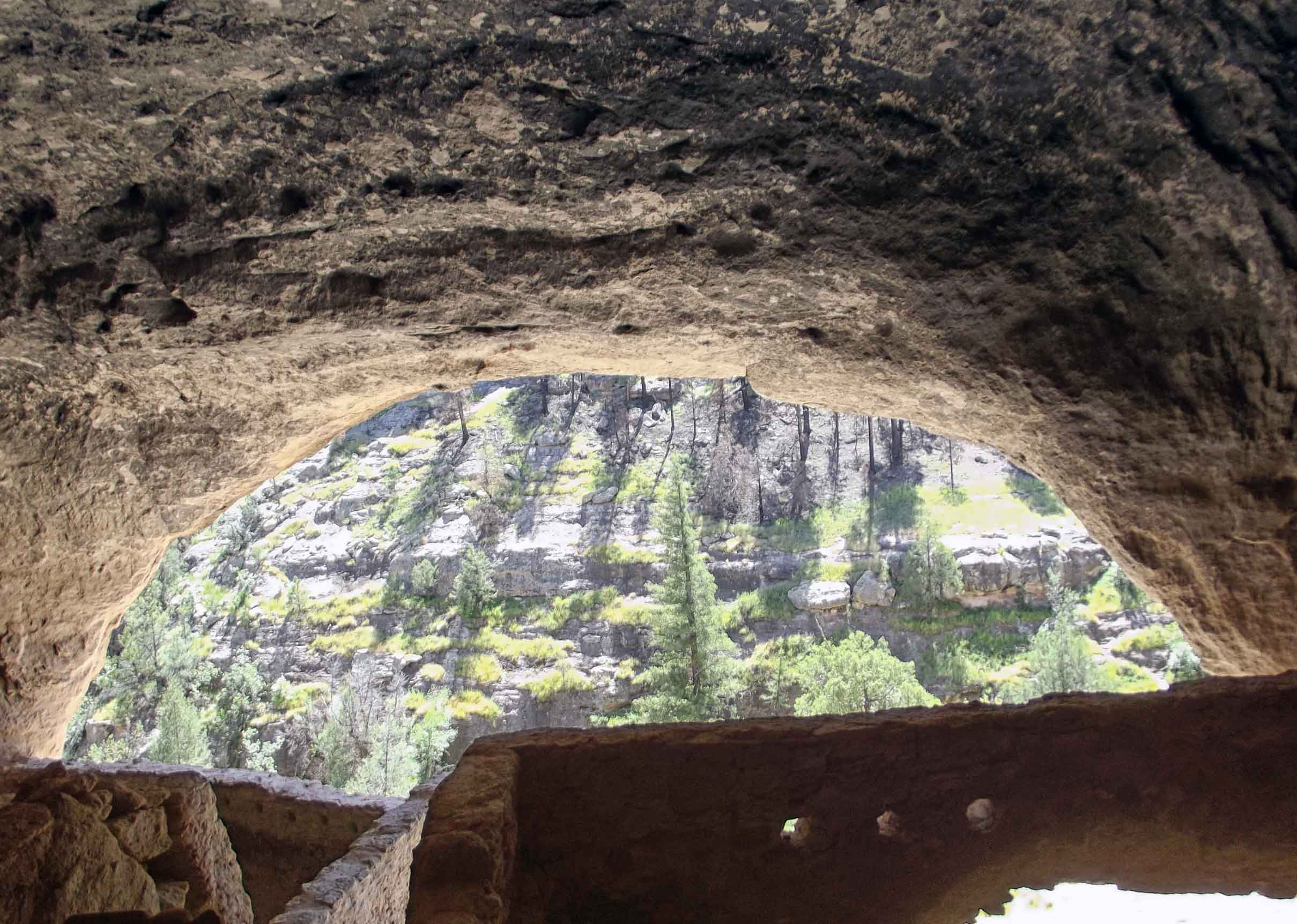 Looking out from a cave with walled structure in foreground