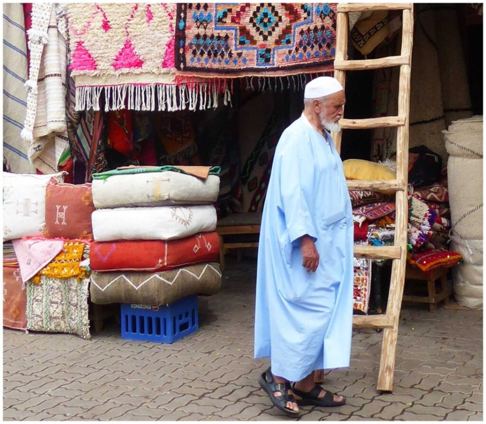 Man in traditional Muslim robes passing a carpet shop