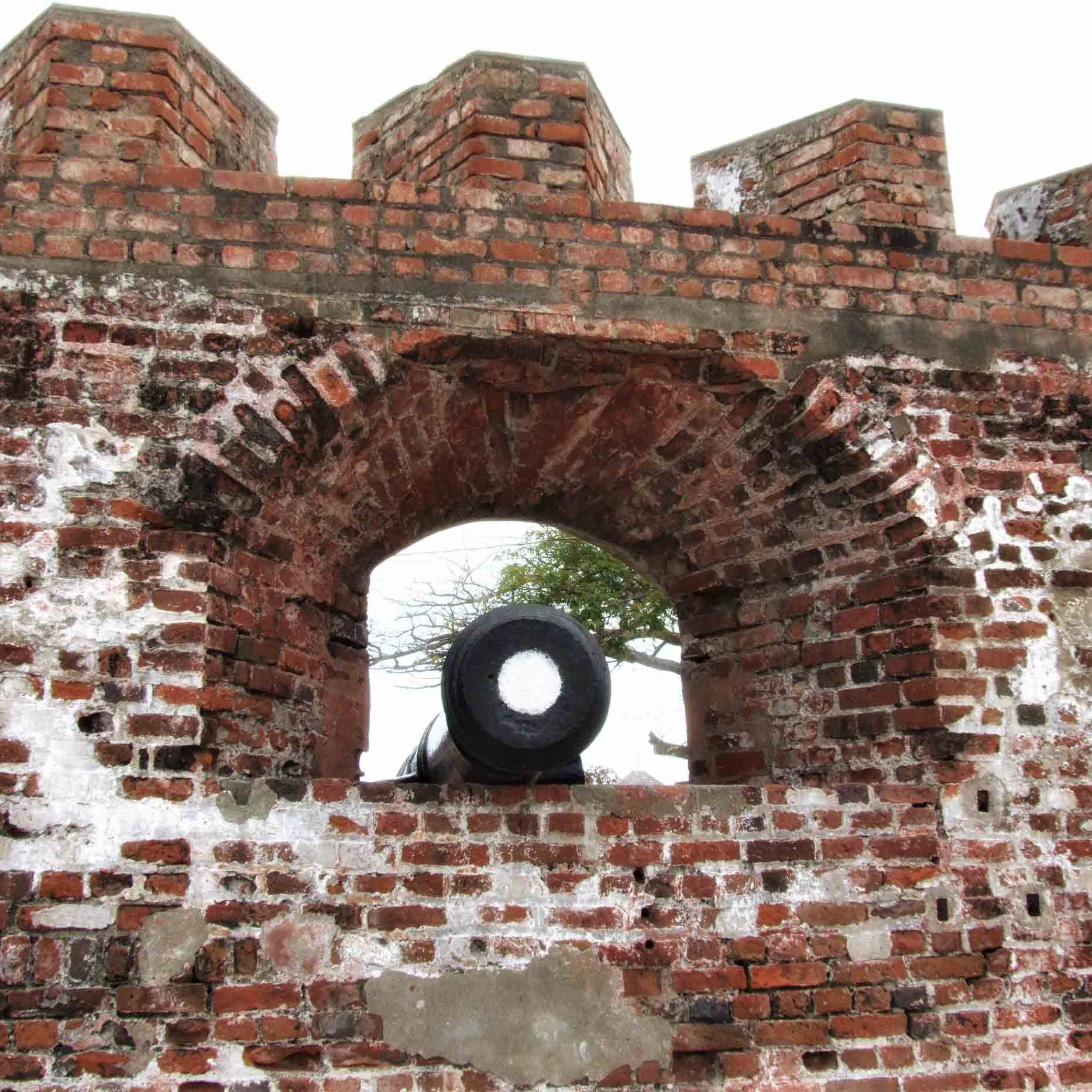 Cannon poking out of brick battlements