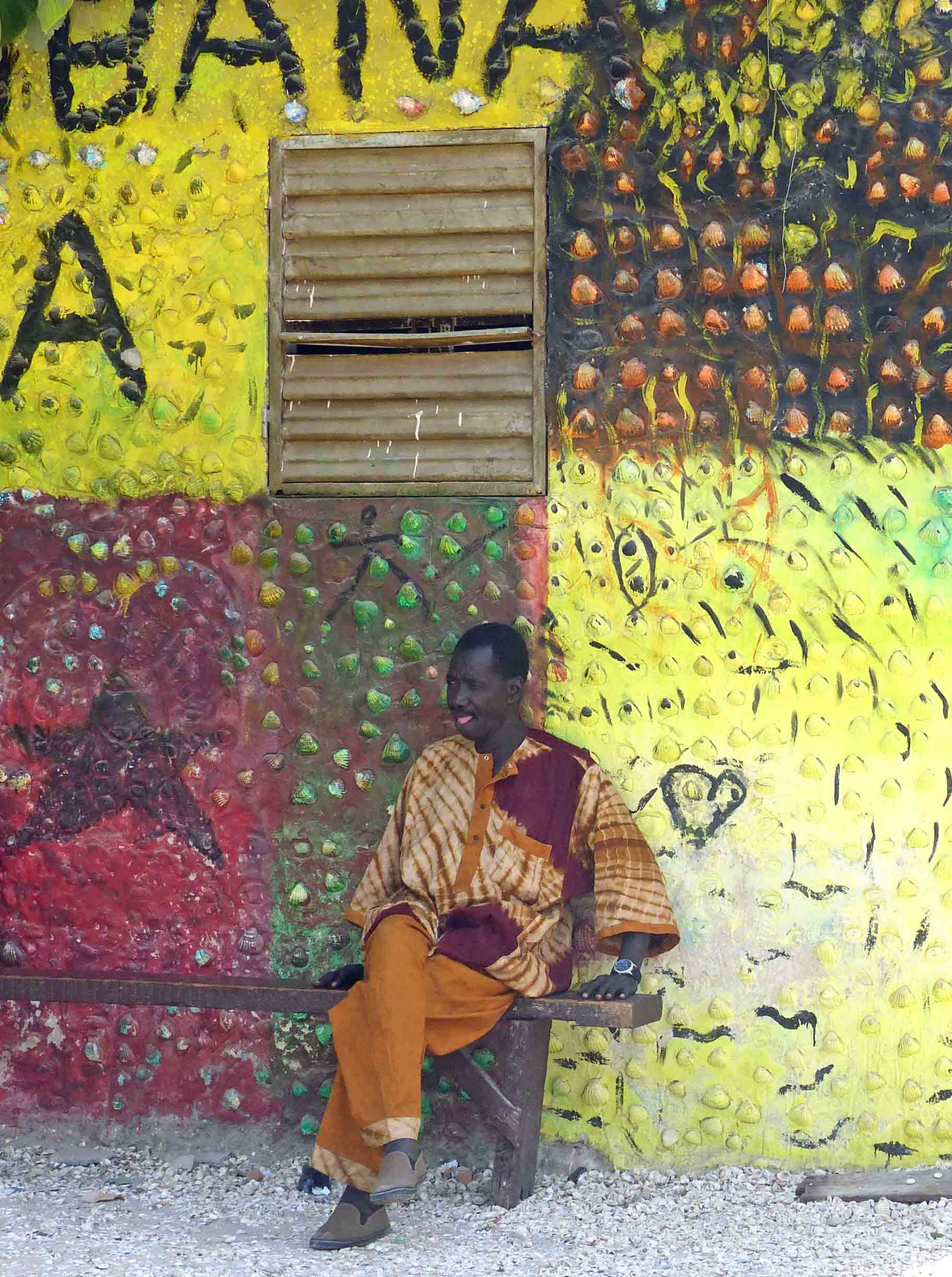 A man in African dress sitting on a bench by a colourful wall