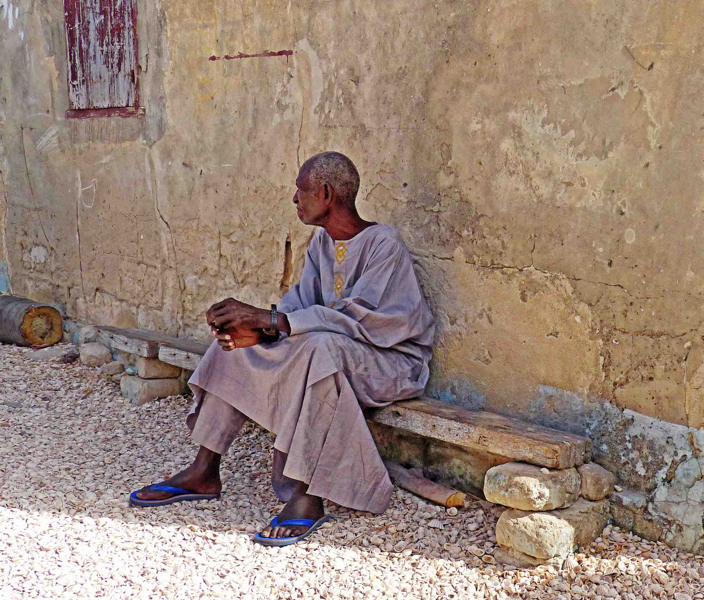 A man in African dress sitting on a bench