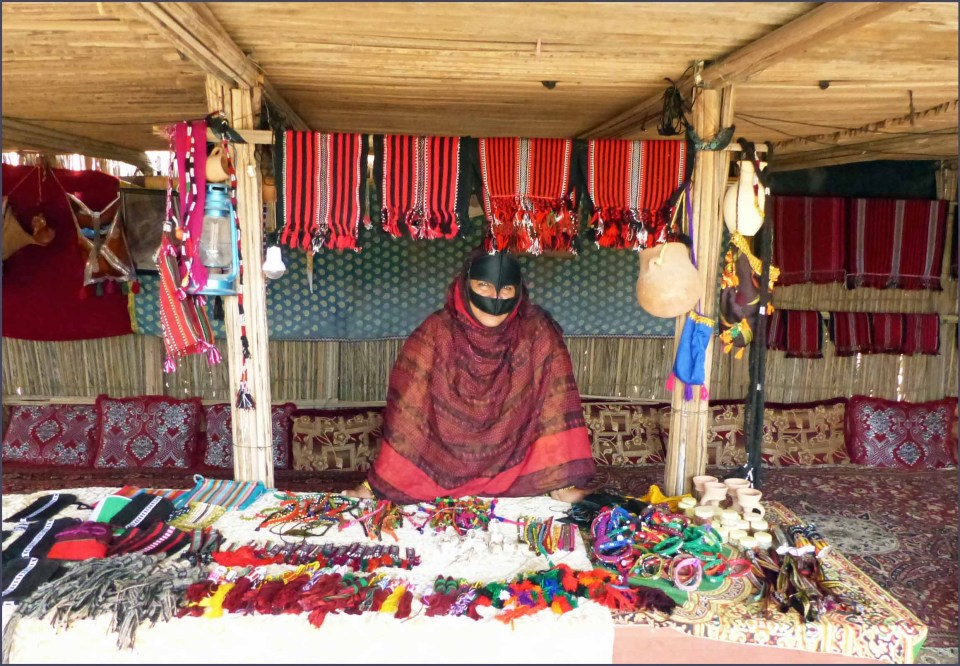 Lady in traditional dress with table of handicrafts