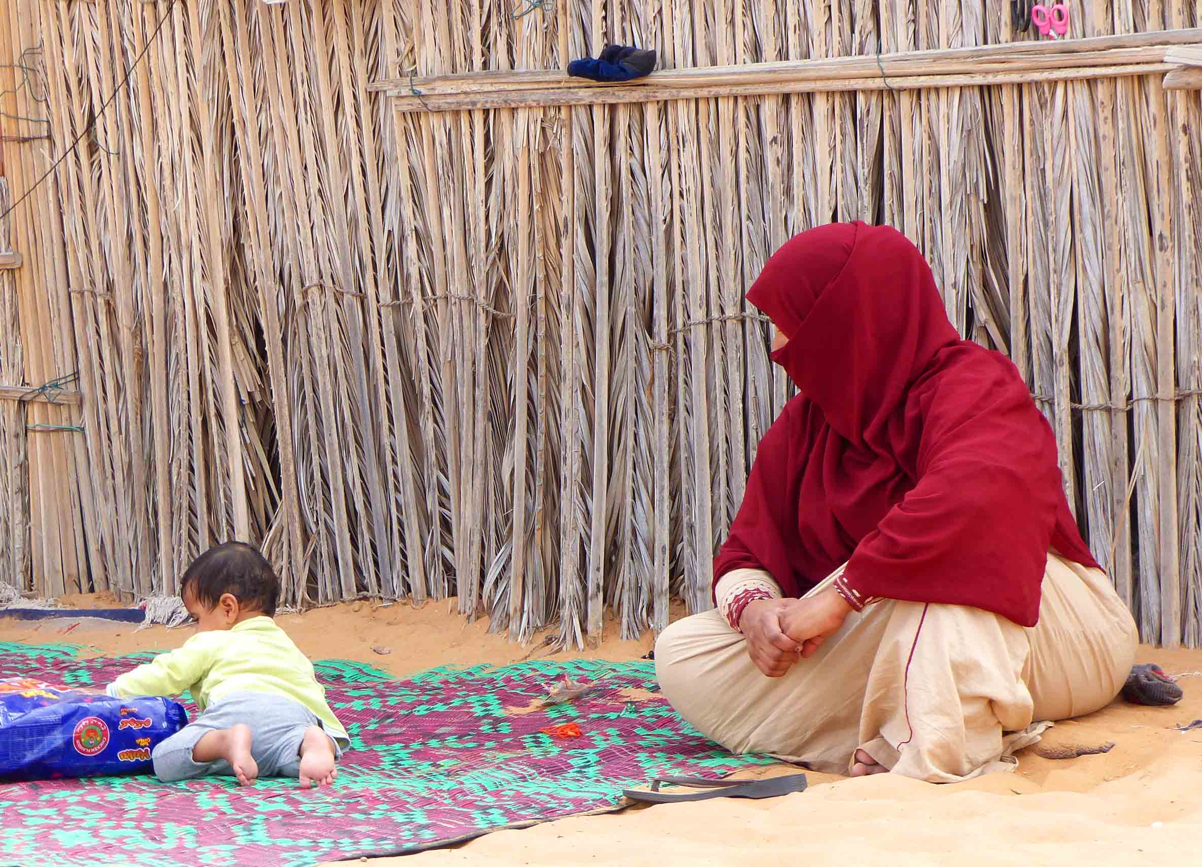 Lady in red hijab watching child playing