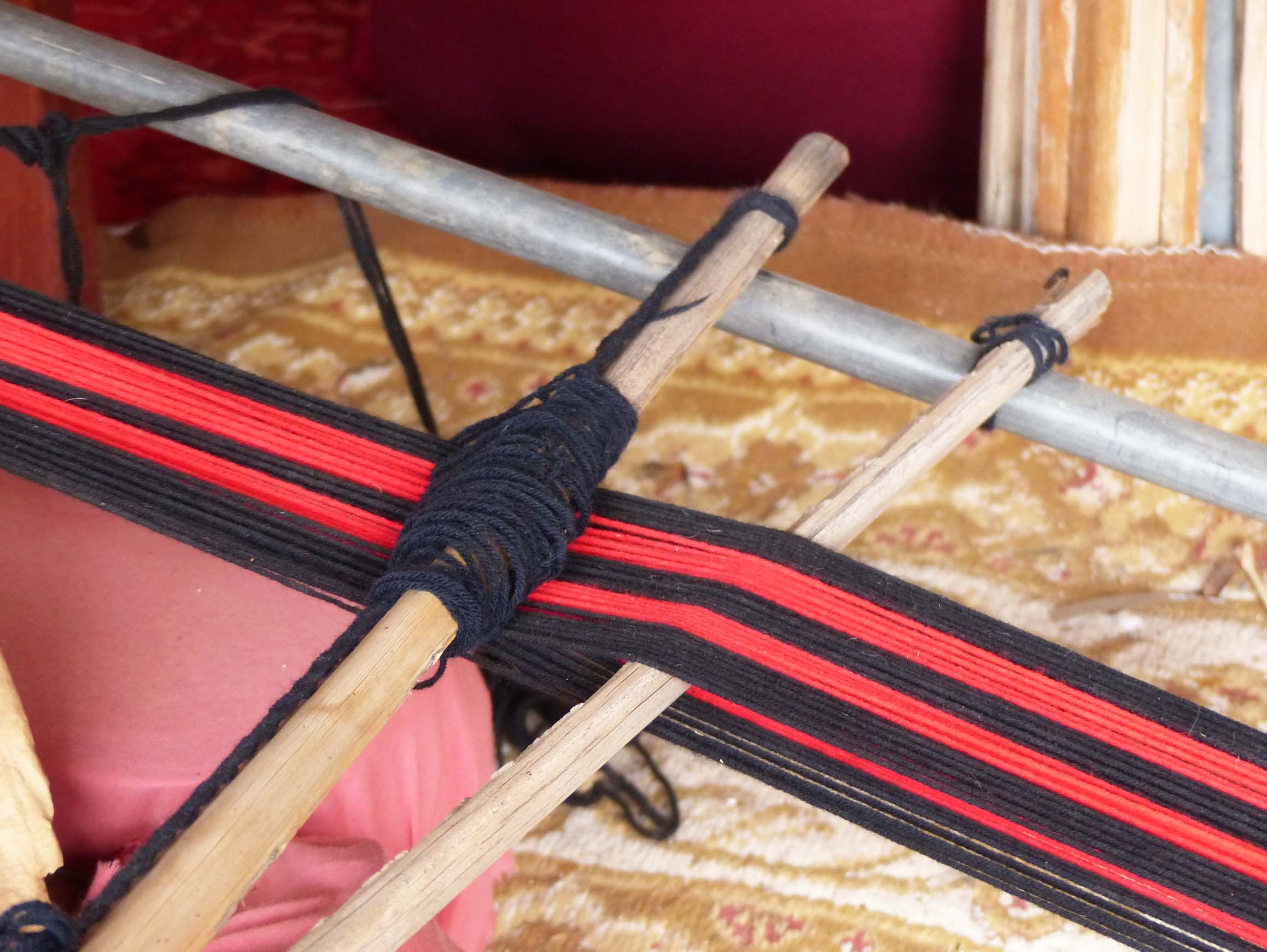 Simple loom with red and black thread