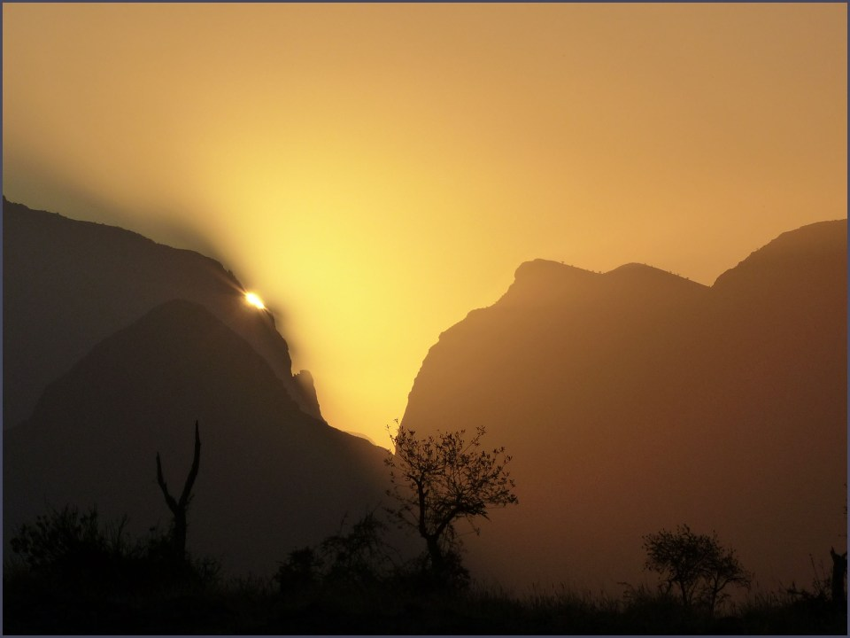 Mountains with yellow sky and setting sun