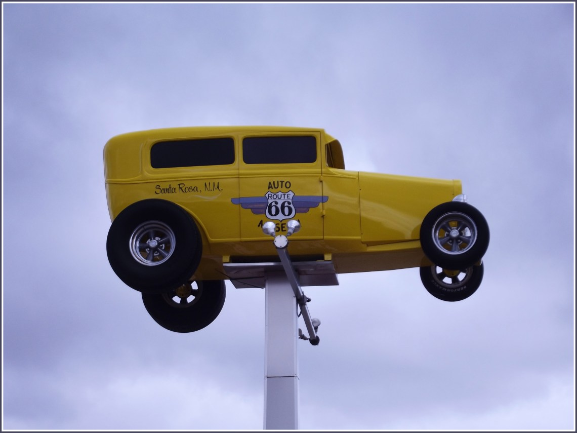 Brightly painted yellow car raised on a platform