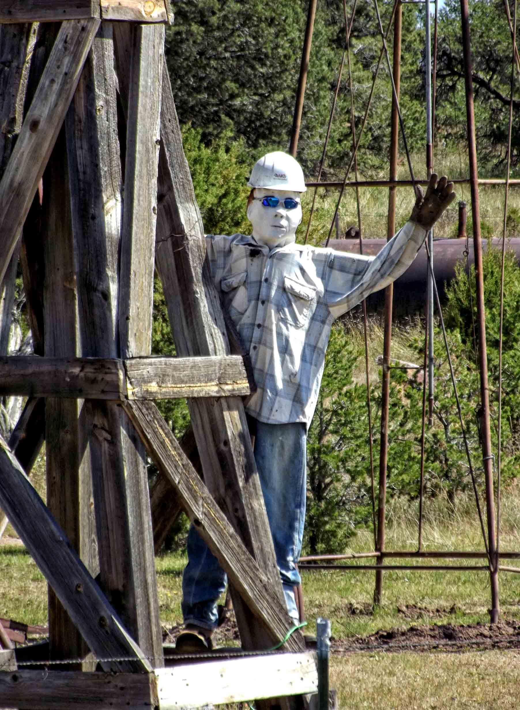 Model of man in lumberjack shirt and hard hat