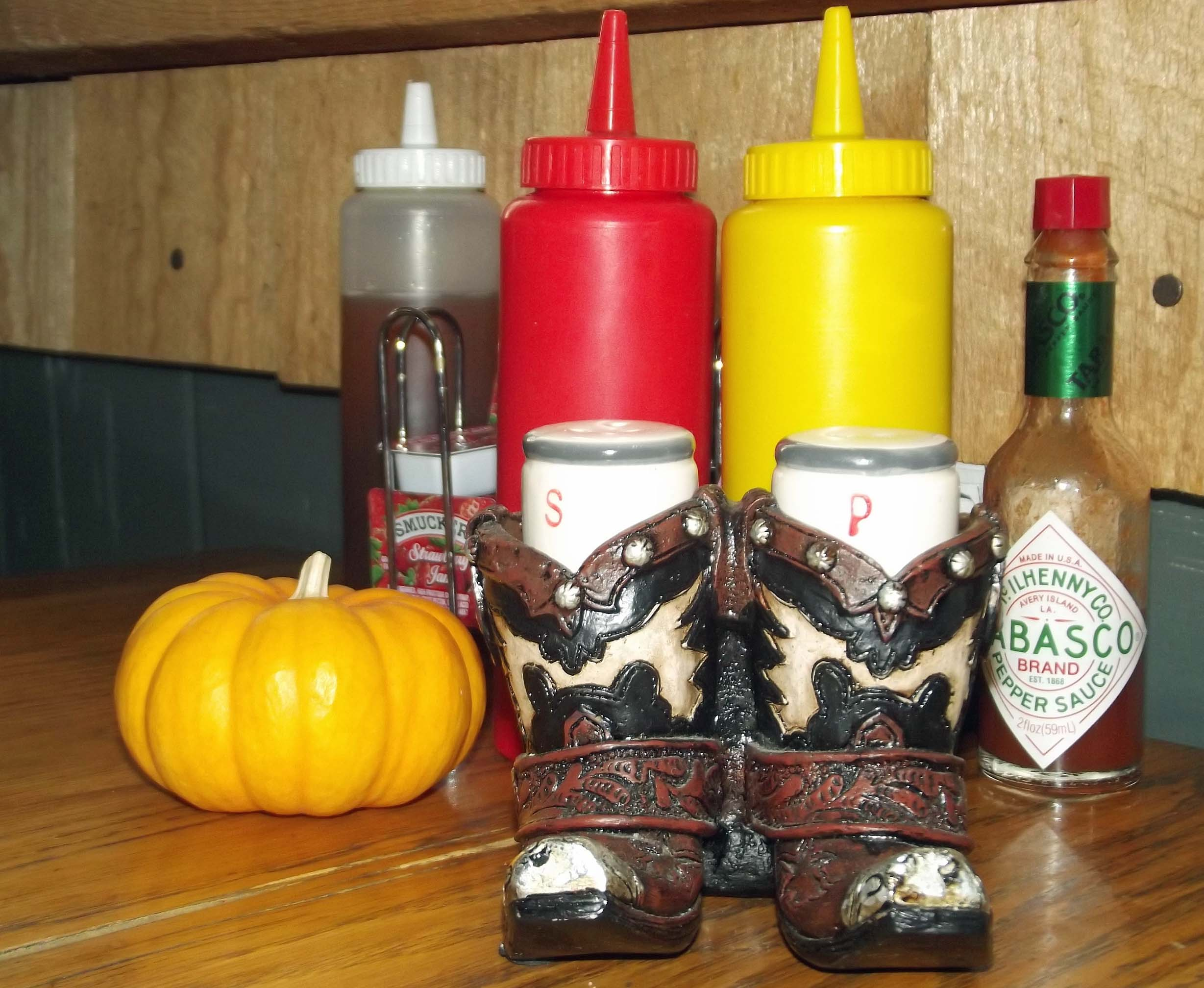 Table with sauce bottles and cowboy boot salt and pepper pots