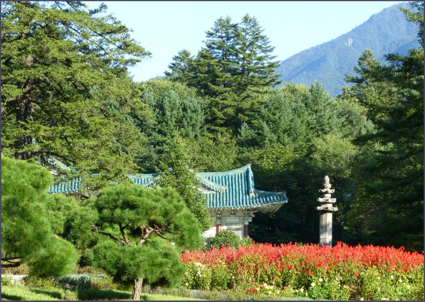 Garden with temple roof and mountain beyond