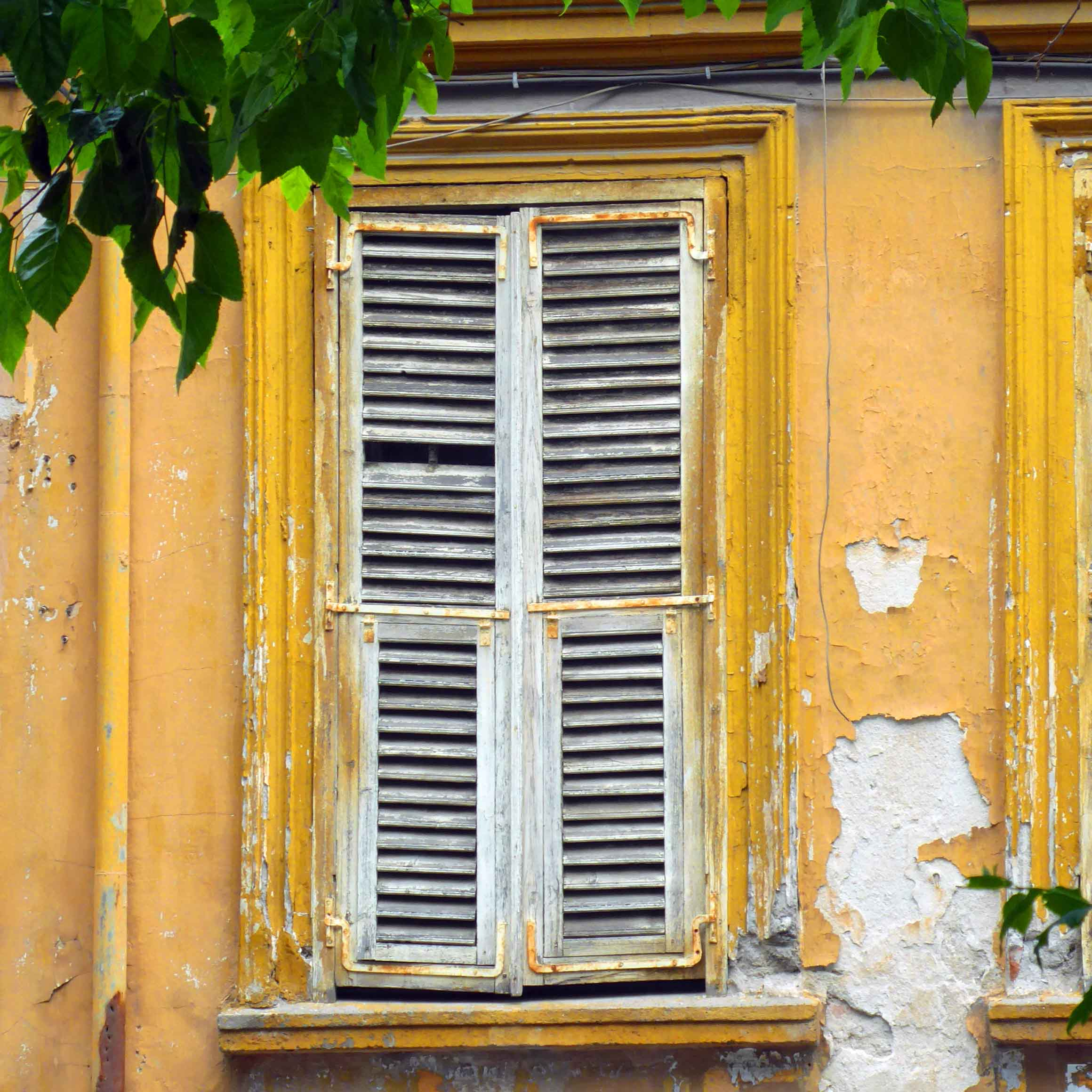 White window shutters and yellow peeling paint on walls
