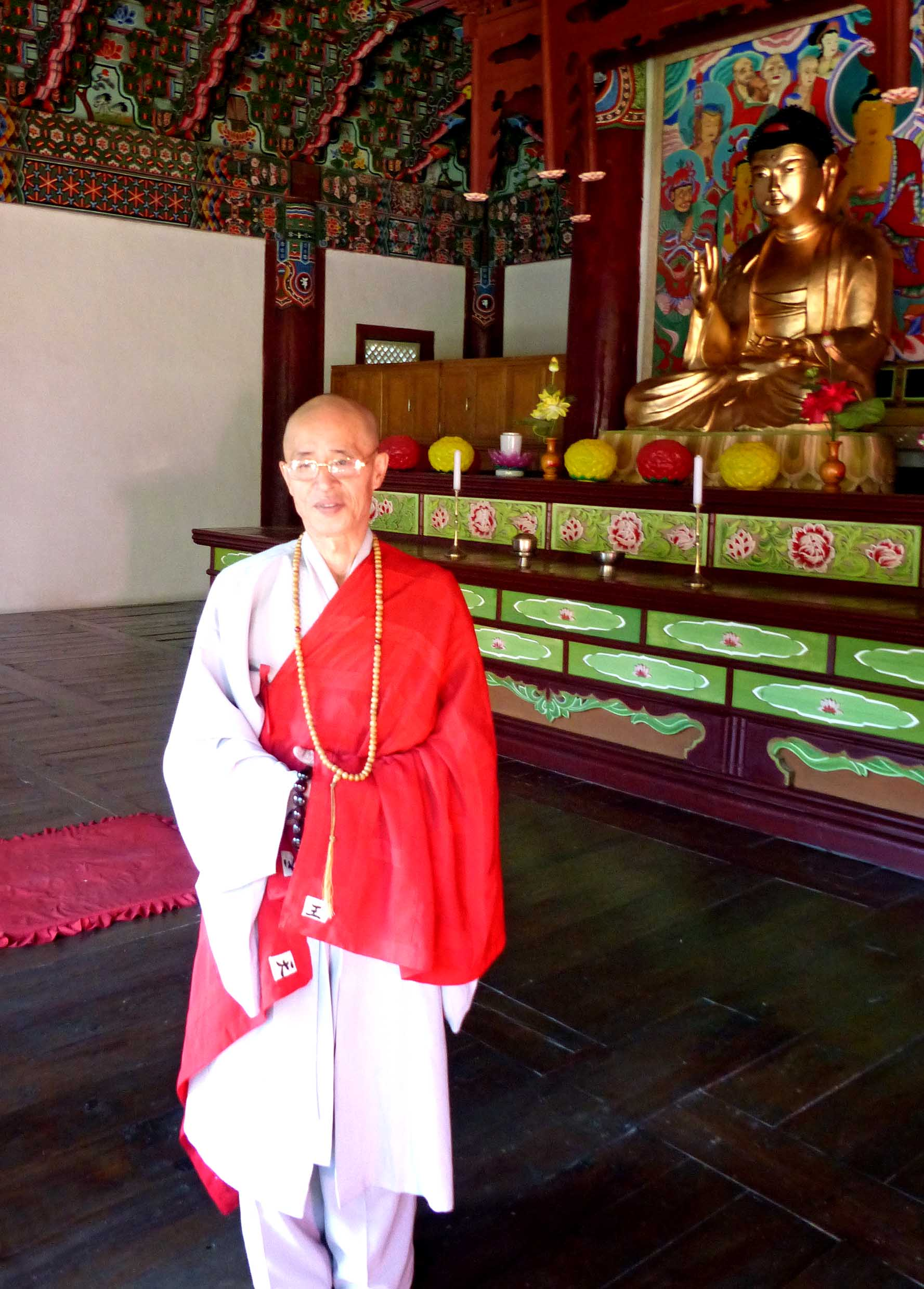 Buddhist monk in front of altar with gold Buddha