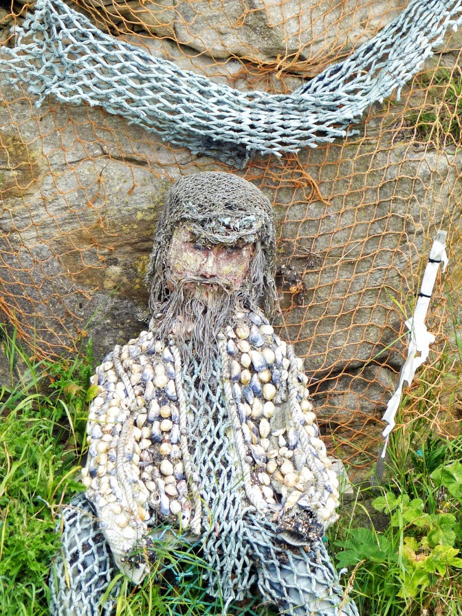 Man made from shells and fishing net propped against a wall