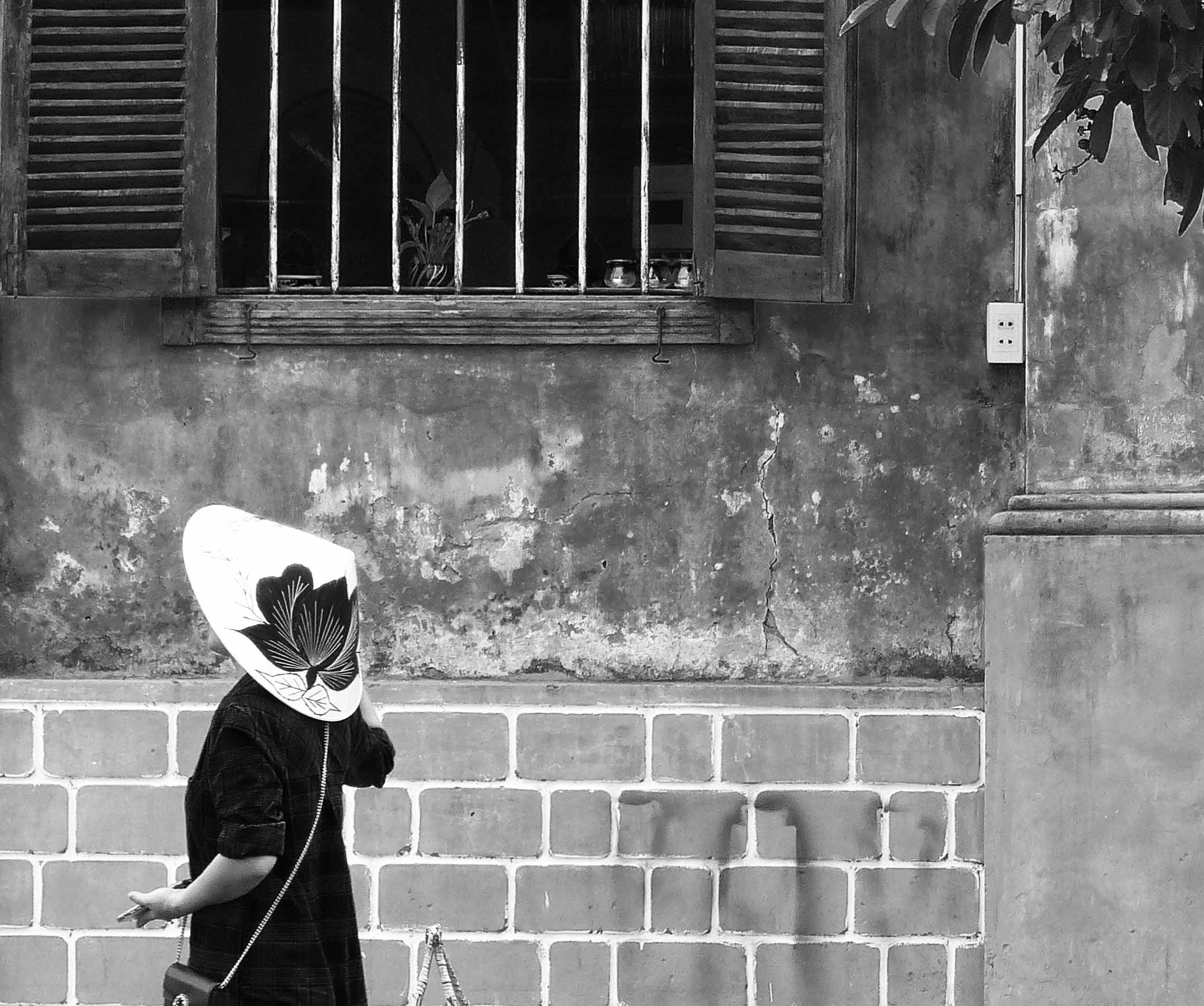 Lady in a hat walking past a building