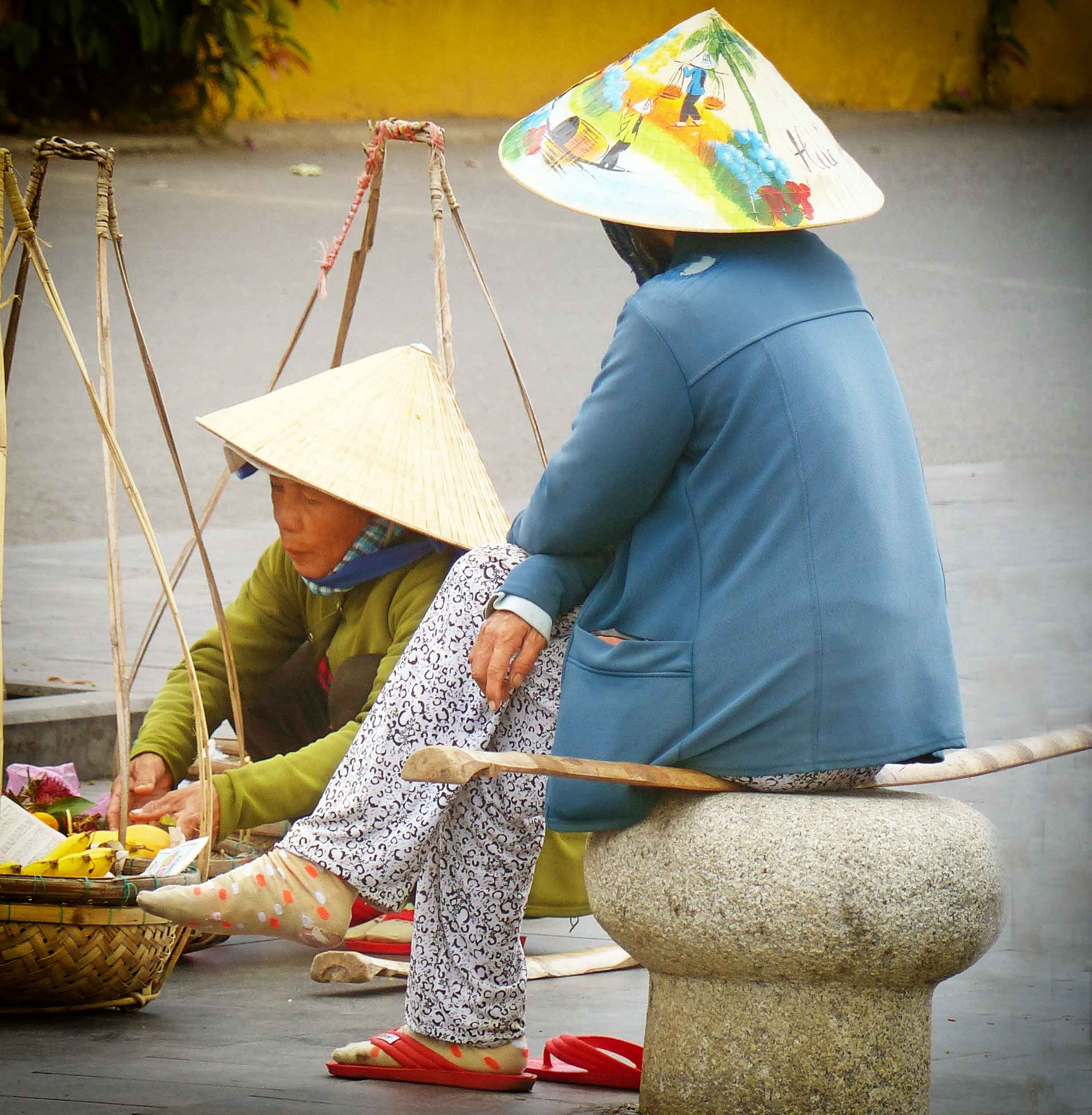 Two ladies in conical hats with traditional baskets on yokes