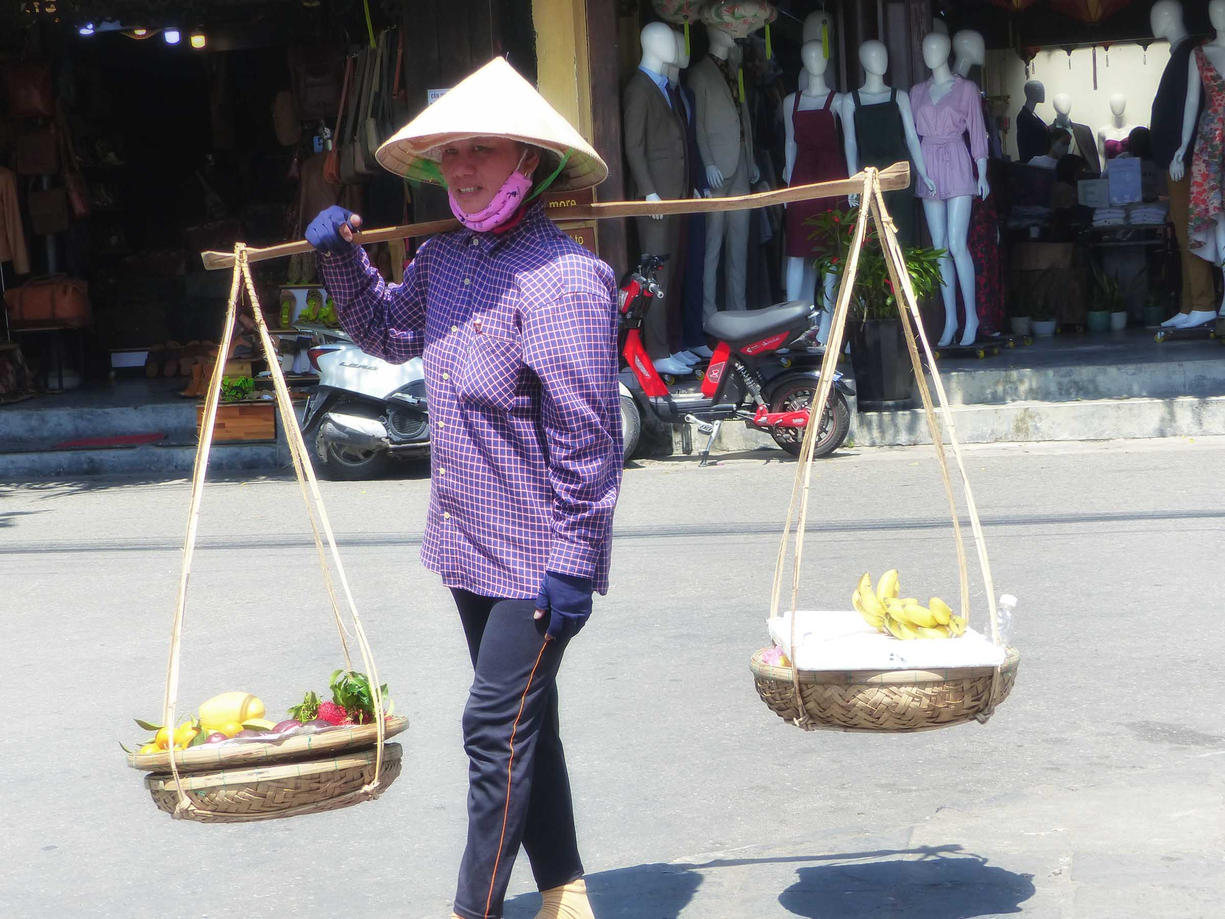 Lady in conical hat with traditional baskets on yoke