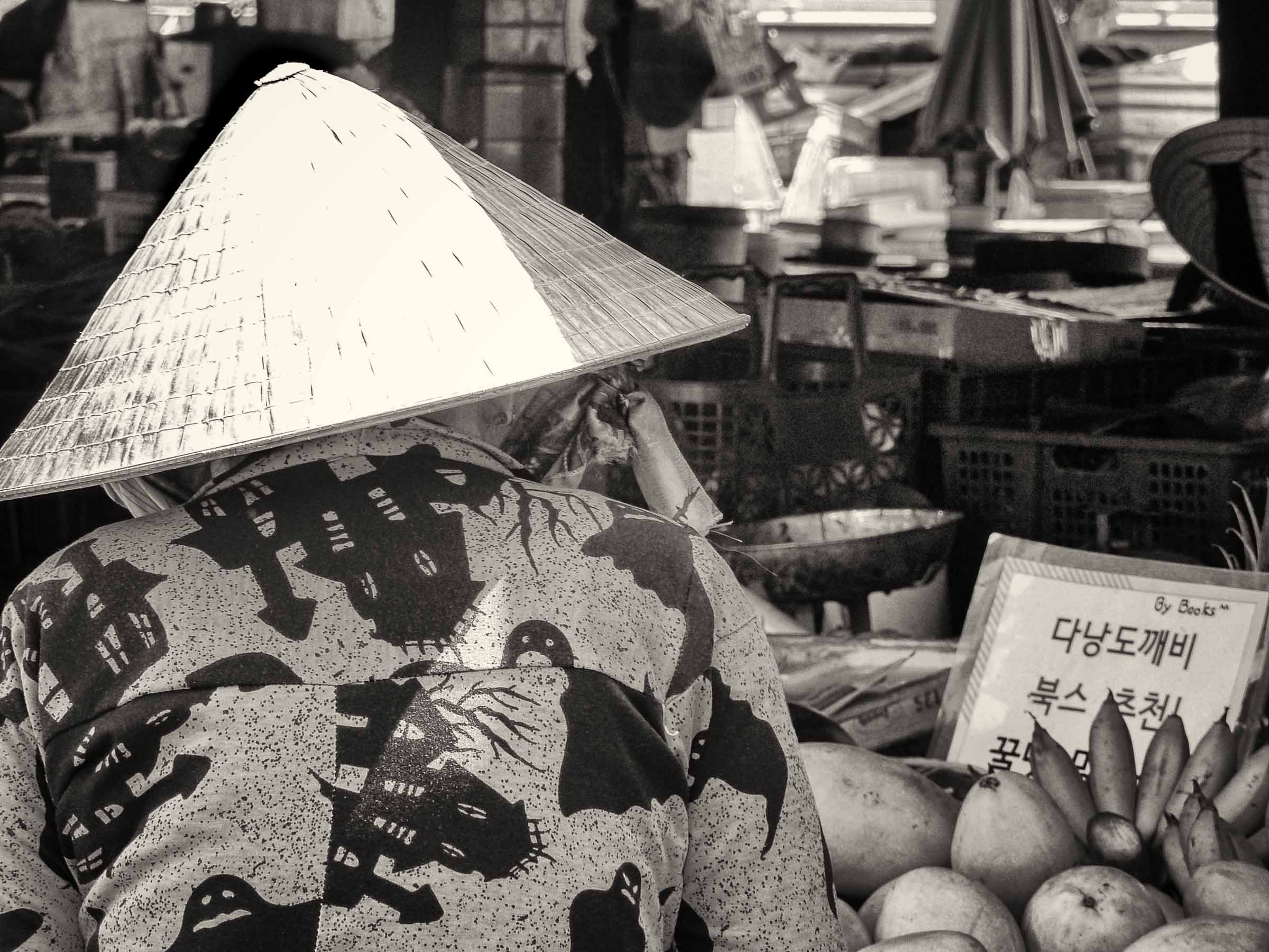 Lady in conical hat at a fruit stall in a market