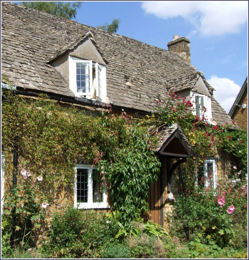 Yellow stone cottage with roses growing around it