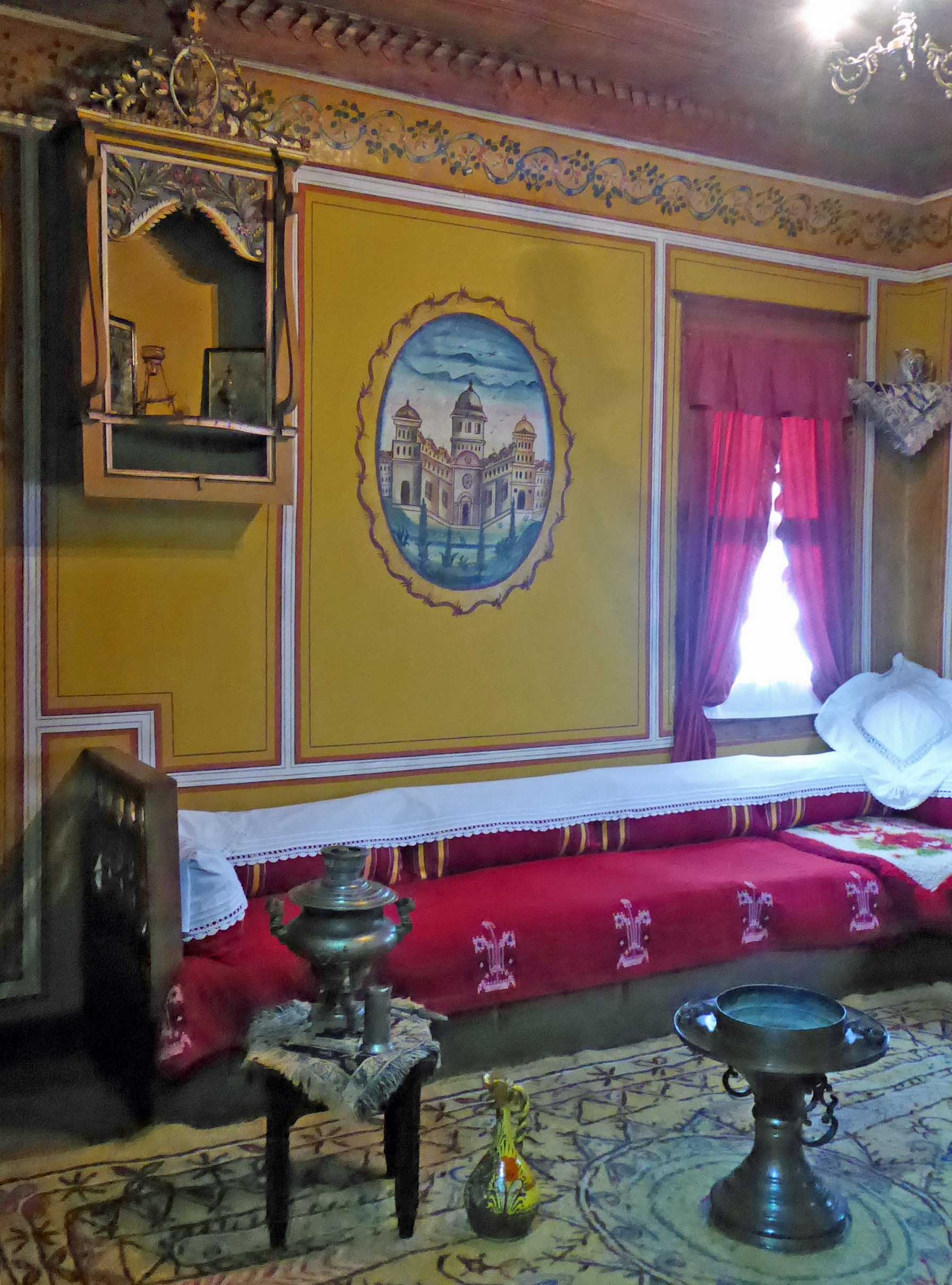 Room with painted yellow walls and red bench