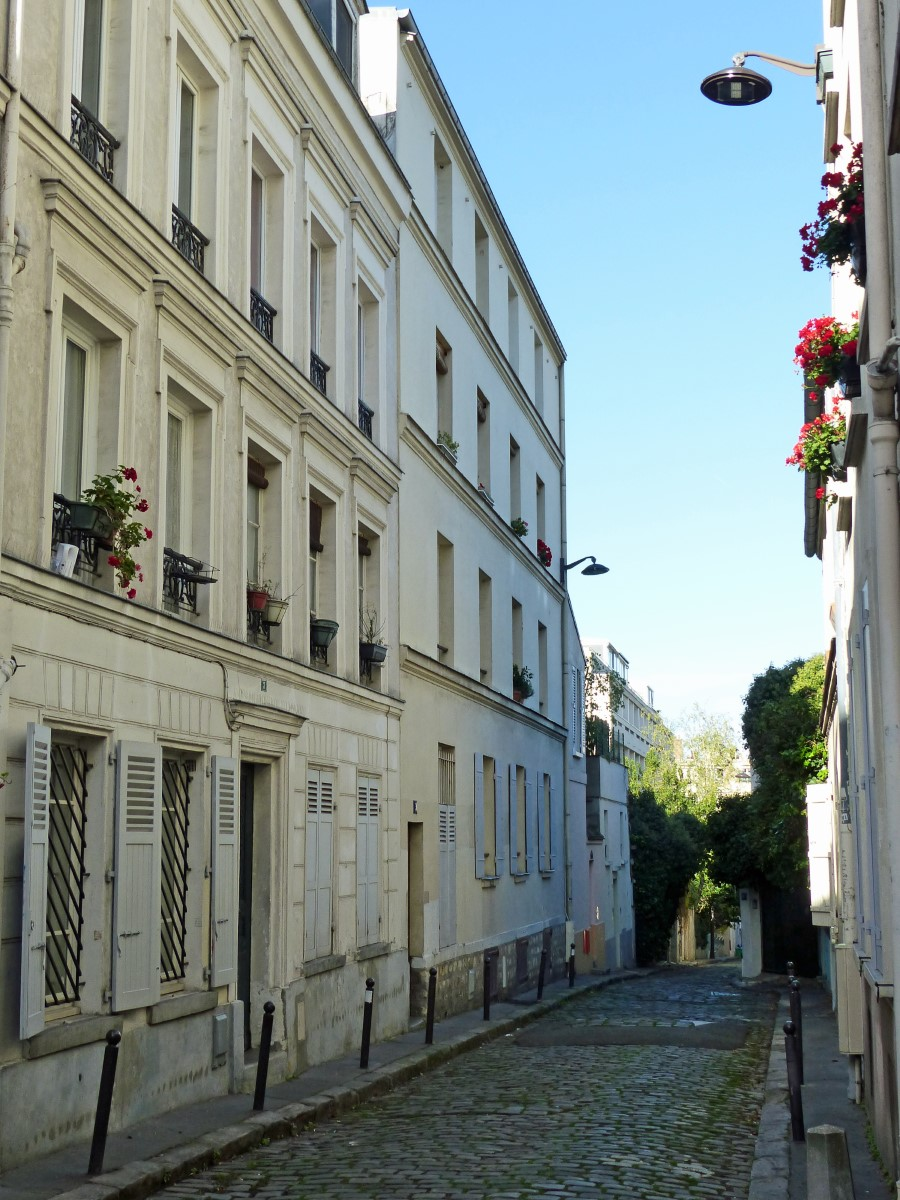 Cobbled street lined with cream painted houses