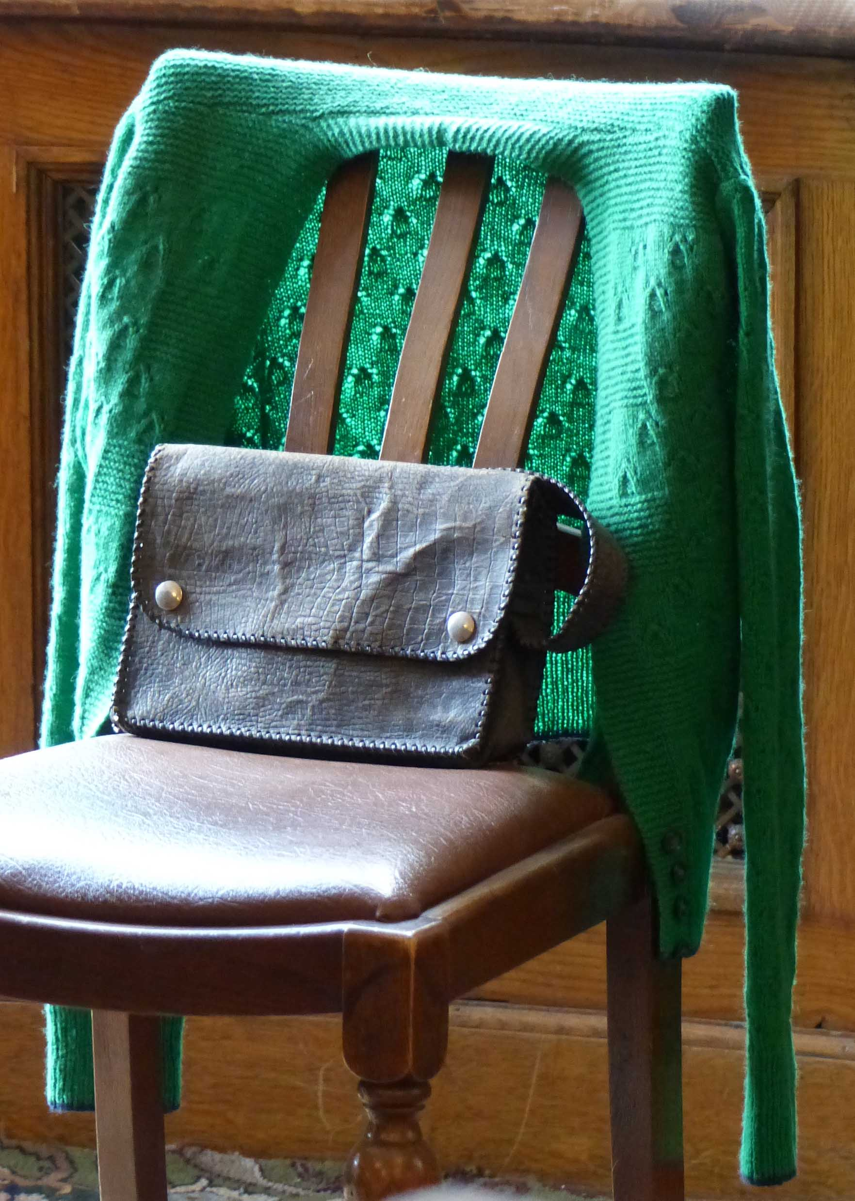 Old chair with green cardigan and small handbag