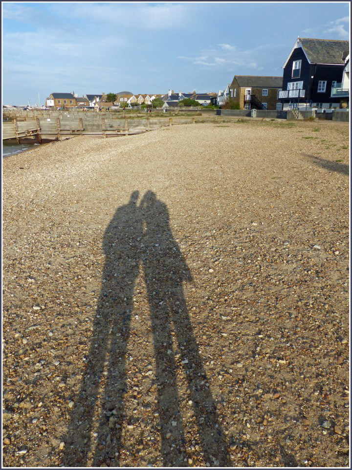 Shadows of couple on pebble beach