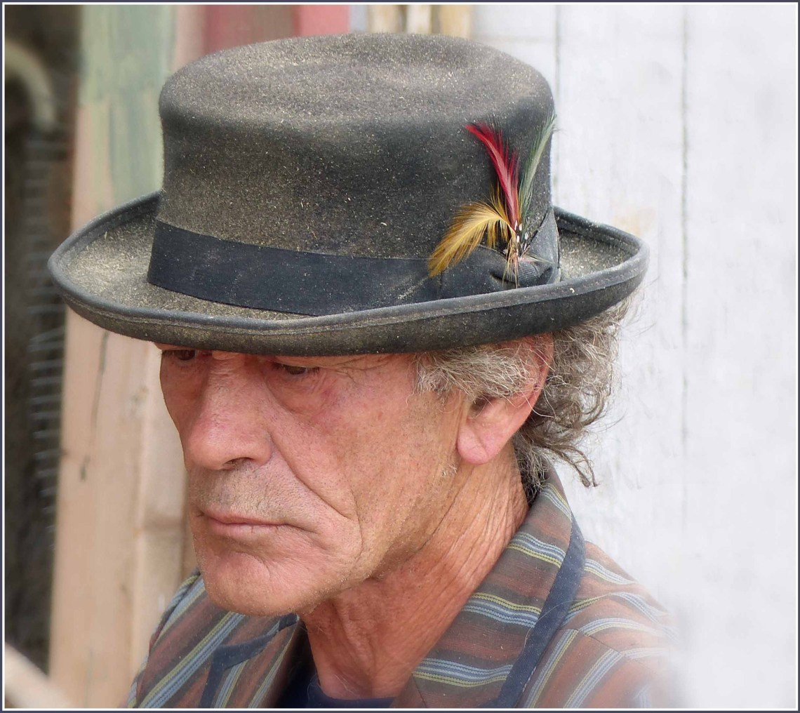 Man in a brown hat with a feather