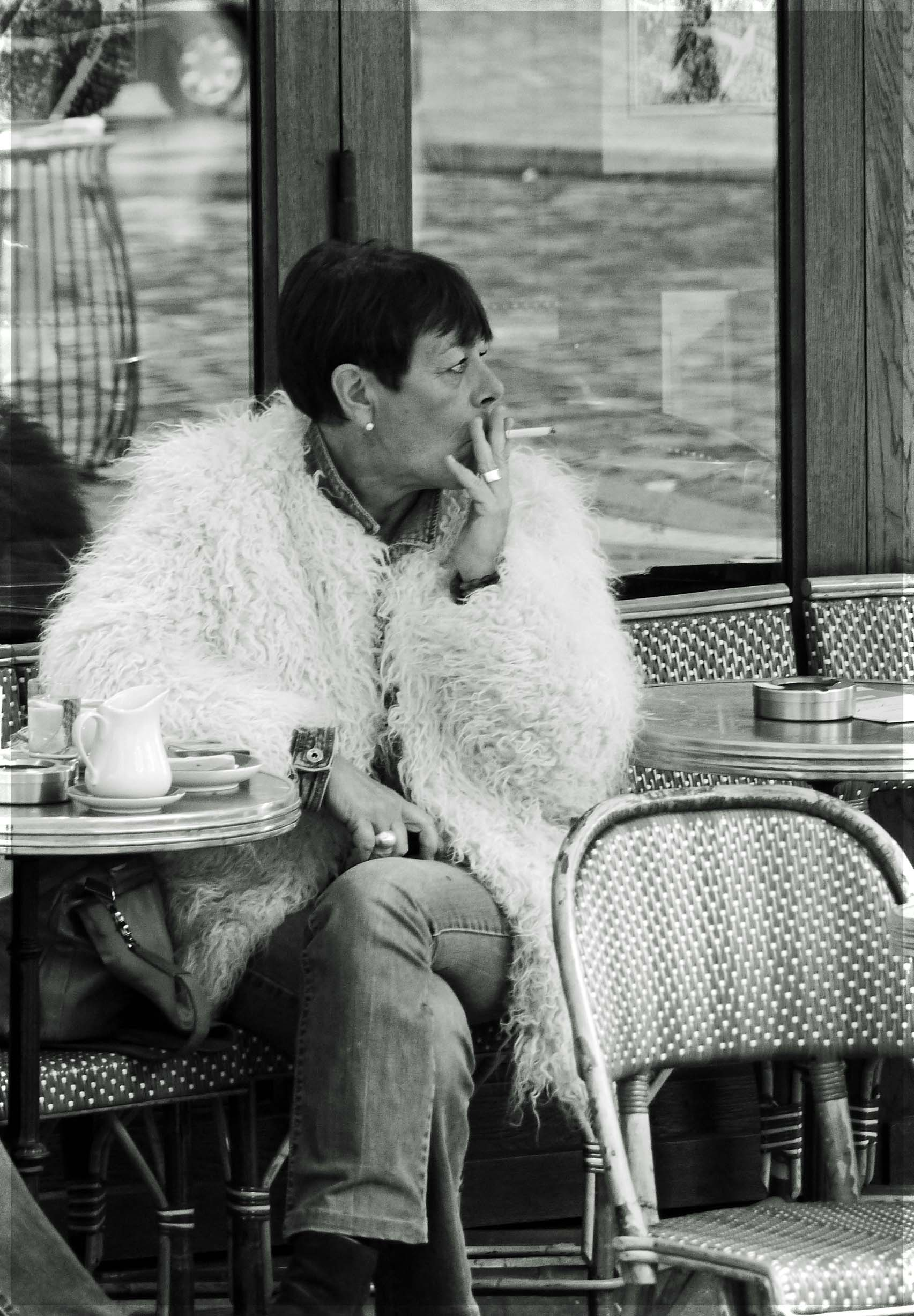 Black and white photo of lady smoking at a cafe table