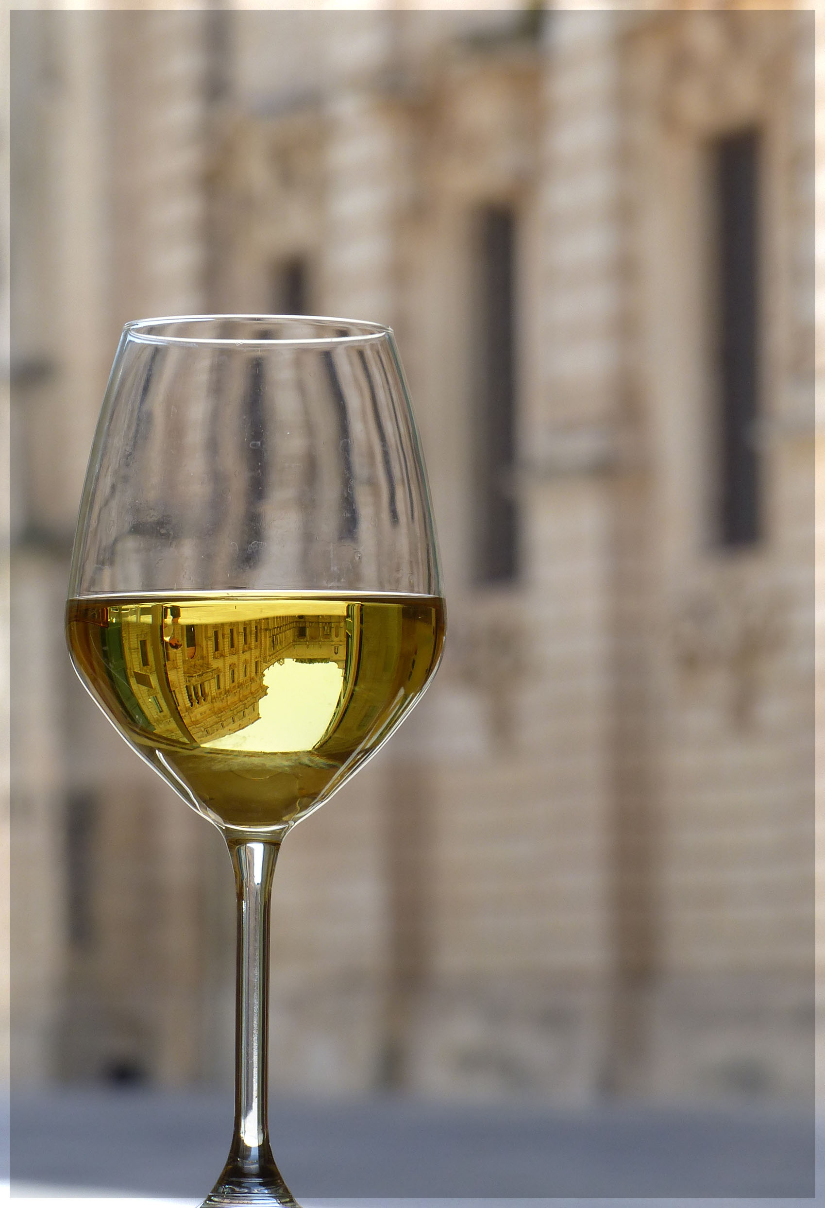 Glass of white wine with old buildings behind